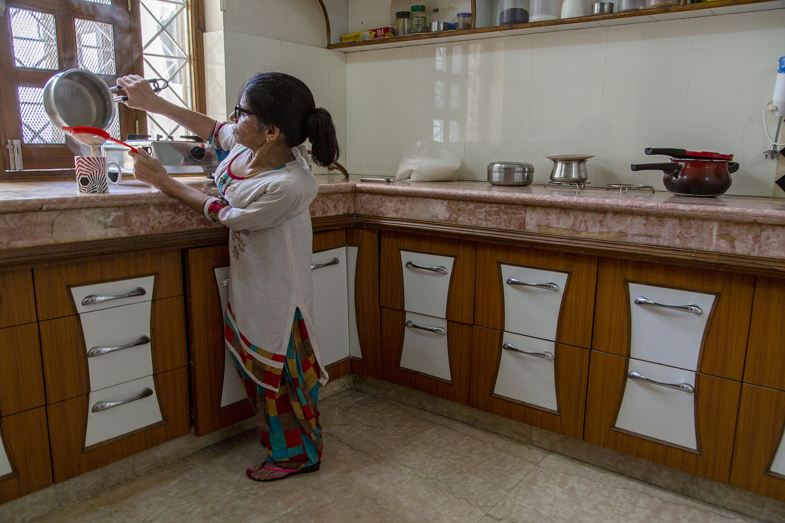 Kavita is making tea in her kitchen. On top of the pink marble platform are steel vessels and a gas stove. Below the platform are many wooden drawers with steel handles. Kavita is pouring tea from an aluminium pan through an orange coloured strainer into a mug.