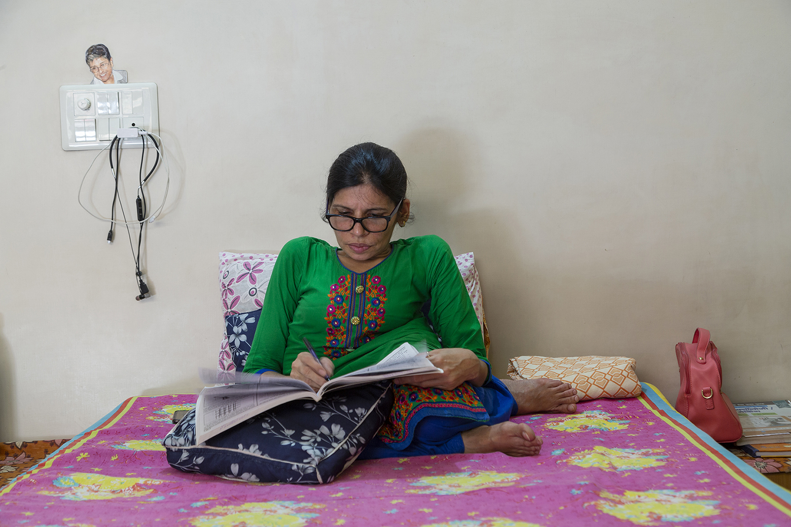 Kavita is sitting up in bed, leaning against a pillow, with legs crossed. She wears a parrot-green kameez with embroidery on the front, and a dark blue salwar. She is writing in a large book resting on her lap. High up on the bare wall, to the left, is a switch panel. A cutout portrait photo of Kiran Bedi sticks out from behind the switch panel.