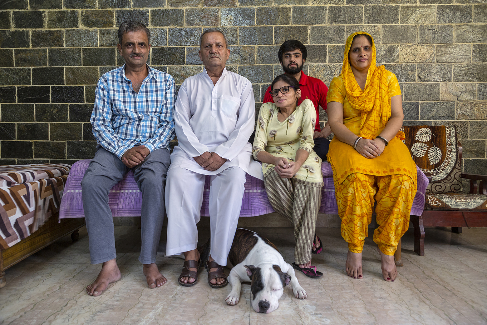 Kavita and her family sit in a row on a deewan. From left to right: elder brother Davender Singh (51), father Pratap Singh (72), Kavita, and sister-in-law Sunitha (46). Behind Kavita is her nephew Abhishek Mathur (22). Dollar is lying near Kavita's feet, front paws spread out, head resting on the ground. Davender wears grey pants and full-sleeve shirt with blue, black and white checks. Pratap wears white kurta-pyjama. Kavita wears a cream kameez and a salwar with brown and cream stripes. Sunitha is in a bright yellow salwar-kameez and her matching dupatta is draped over her head. Abhishek, who has a beard and moustache, wears a red T-shirt.