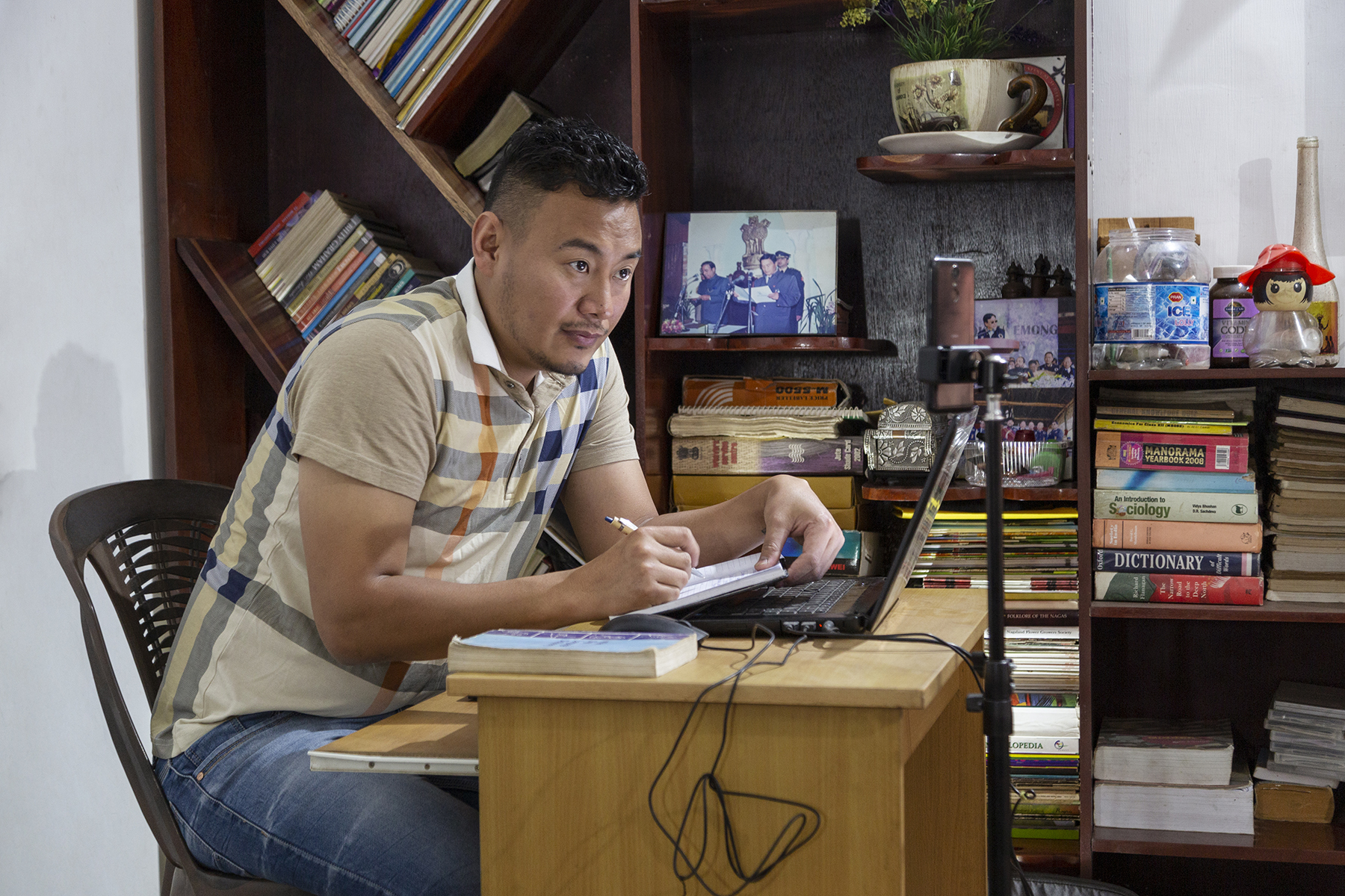 Kilumo wearing light blue jeans and a beige checked shirt sits in a brown plastic chair behind a table, writing something in a book with a pen. The desk is made of beige wood and there is an open laptop on it. Behind him is a large wooden rack with books.