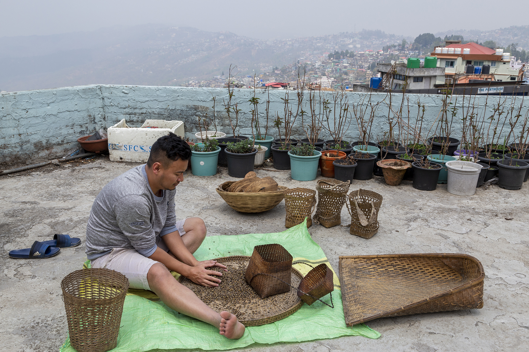 Kilumo wearing a grey T-shirt and beige shorts sits on the ground on the terrace, legs outstretched, cleaning dry brown seeds. There are several woven cane items around him, including a large winnow and small baskets. Several flowerpots containing plants with barely sprouting leaves are clustered next to one of the low terrace walls painted pale blue. In the background are mist-covered houses on hills.