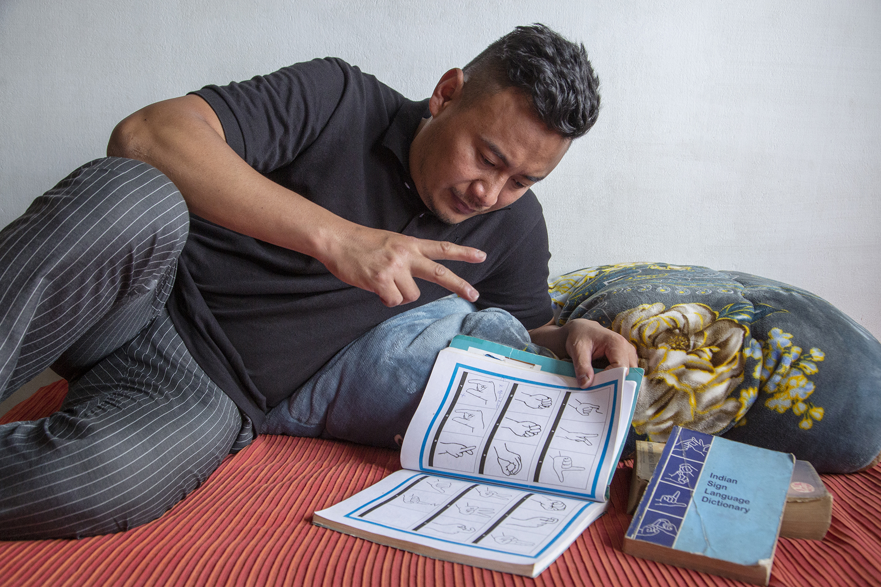 """Kilumo Ezung, in black T-shirt and black pants with grey pinstripes, is relaxing on a bed covered with a reddish orange bedsheet. He is lying on his side, left arm propped up on a pillow and left hand holding open a book with figures of hand signs outlined in black. He is gazing into the book and mimicking one of the figures by making a V sign with the fingers of his right hand. Next to this book is a thick book with a blue cover that says """"Indian Sign Language Dictionary""""."""