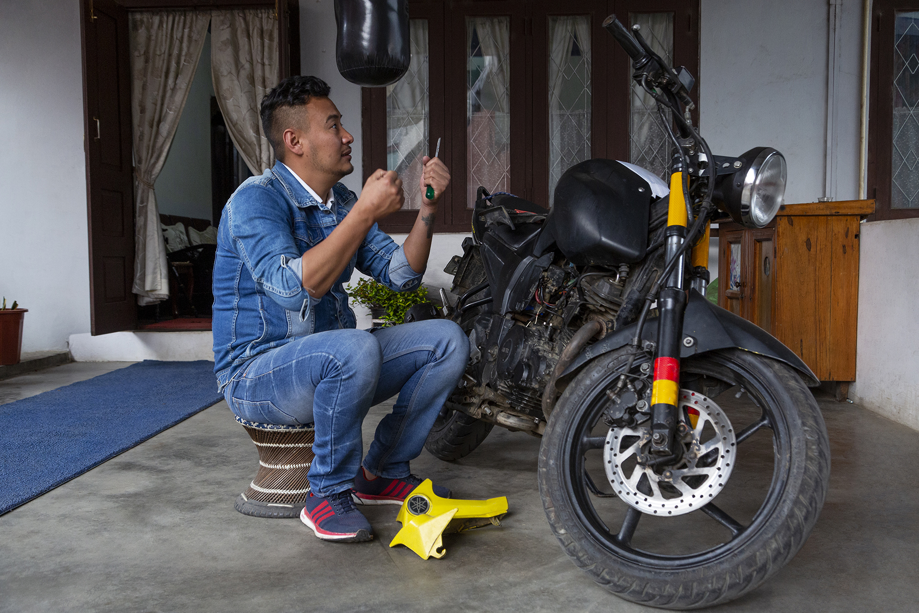 Kilumo in sky blue denim shirt and matching blue jeans is indoors, repairing his black motorbike. His arms are bent at the elbow as he holds up a screwdriver that he grips with his left hand, while his right hand is clenched in a fist.