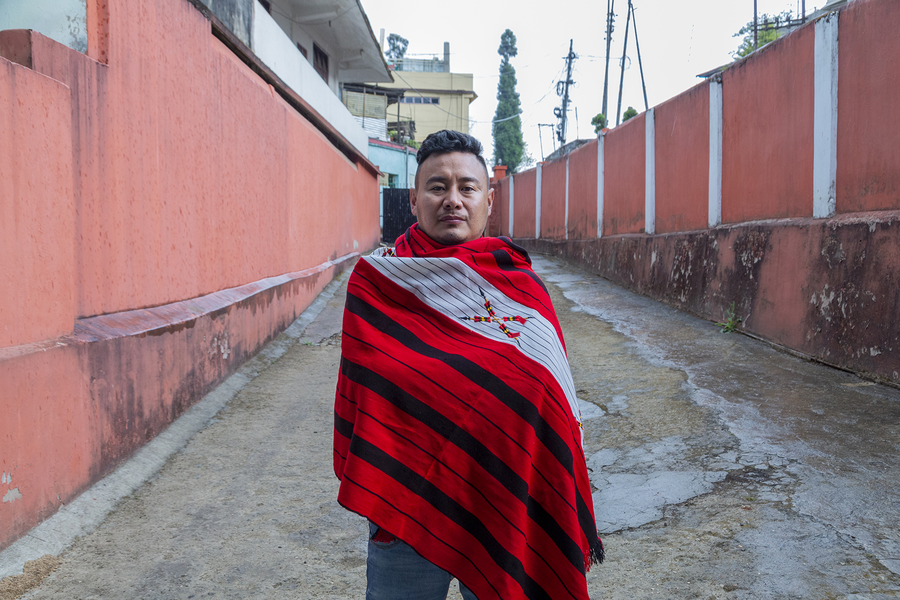 Kilumo stands outdoors on a concrete surface between two terracotta painted walls that stretch lengthwise on either side. A red Naga shawl is wrapped around him, covering his body till his thighs. The shawl has black, widely spaced, horizontal stripes and an embroidered emblem of two crossed spears on a grey background.