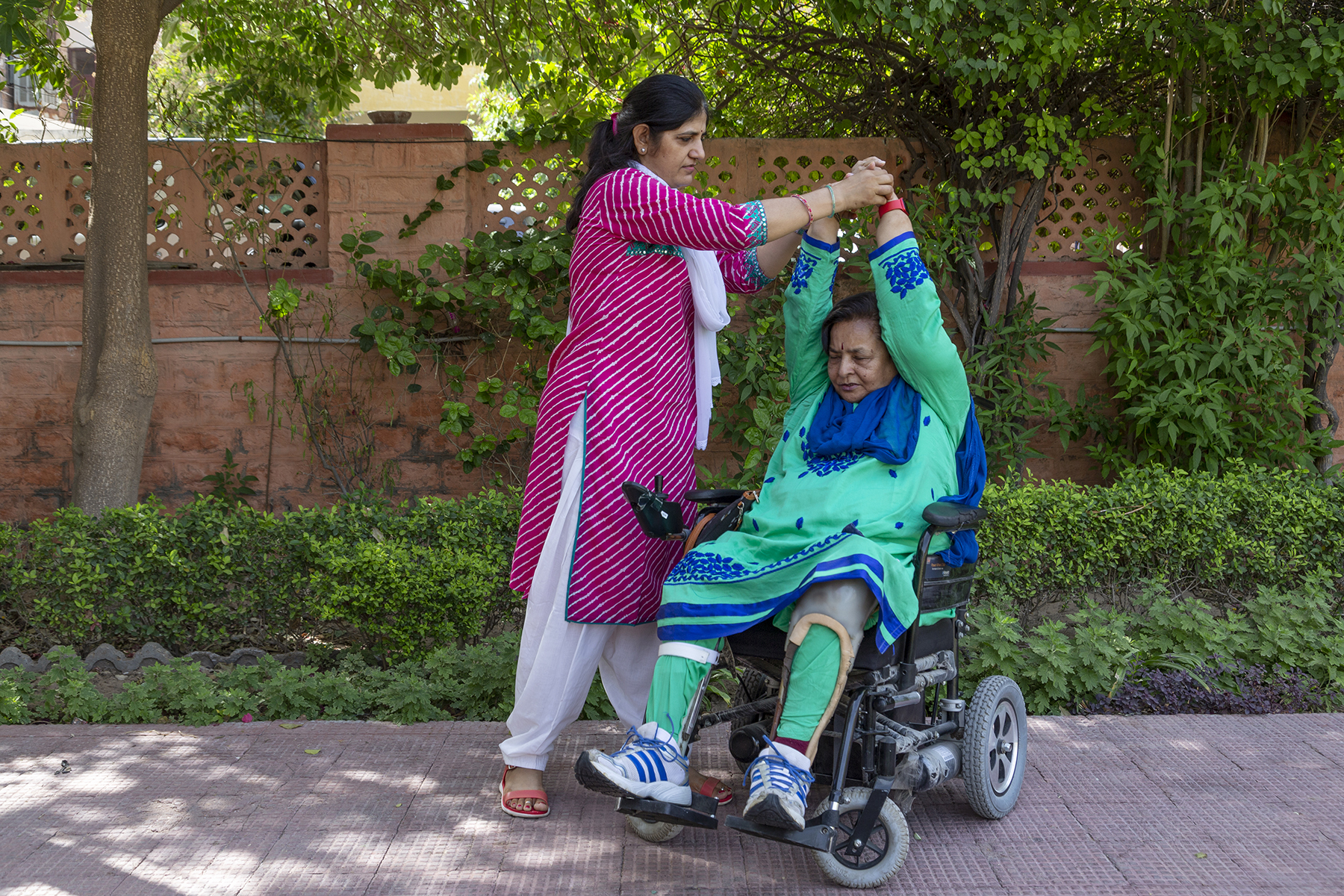 Kusumlata in her wheelchair is exercising in the garden with the help of her student Nirmala Bishnoy. Behind them is a terracotta-colour brick compound wall. Between them and the wall is a hedge of non-flowering plants about a foot high. Nirmala is holding up both of Kusumlata's hands high above her head by grasping her wrists. Nirmala wears a white salwar and pink kameez with thin white diagonal stripes and Kusumlata, a royal blue and sea green salwar kameez with a matching blue dupatta.
