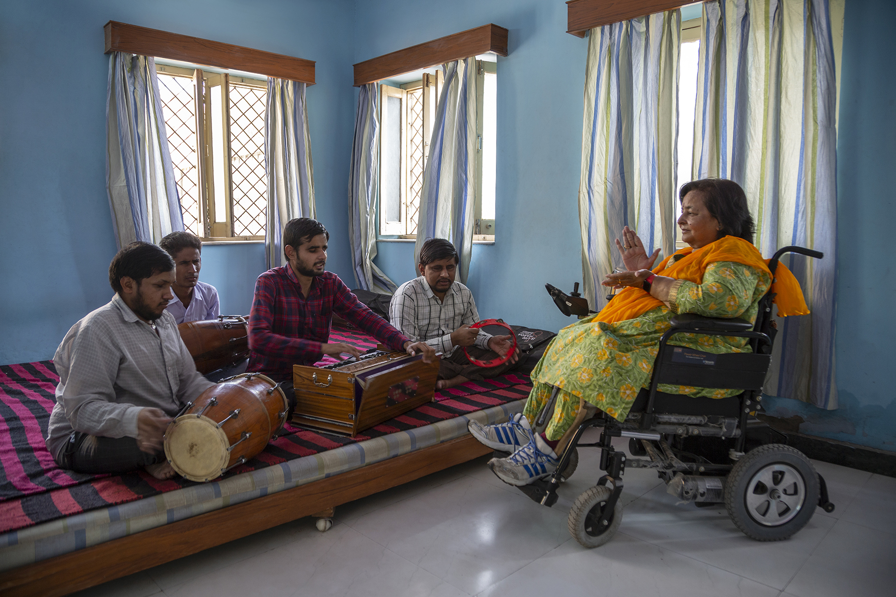 Kusumlata sits in her wheelchair in a room with blue walls and three windows with striped curtains. In front of her is a low wooden divan draped with a red and white striped rug on which four blind musicians sit crosslegged. Two play the dholak (drum), the third plays the harmonium and the fourth, the tambourine. The clapping action of Kusumlata's palms show that she is measuring the beats, keeping taal to the music.