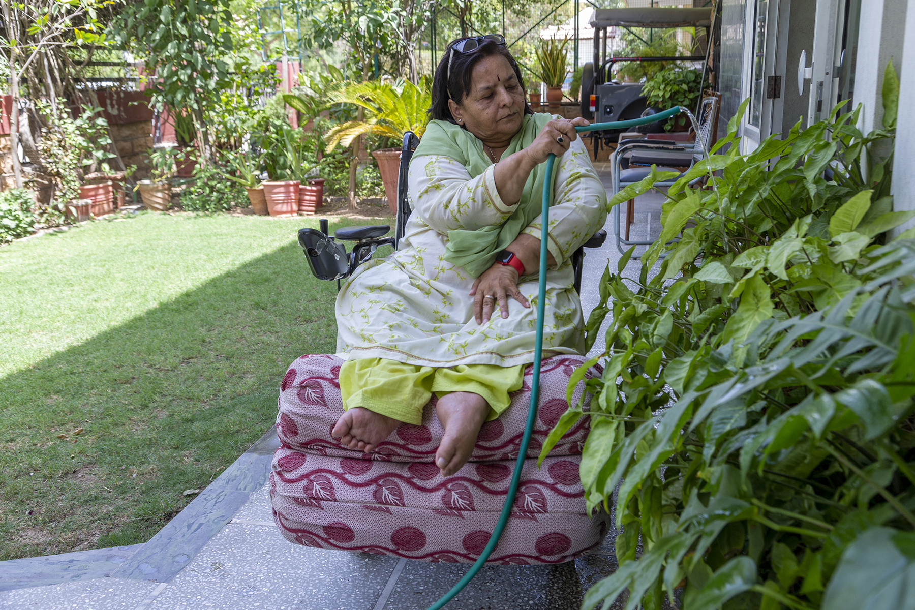 Kusumlata sits in her wheelchair, wearing a pale green salwar kameez and pista green dupatta, watering the leaves of a row of potted plants to the right, using a dark green rubber hosepipe. To the left is a green patch of lawn bordered by potted plants.