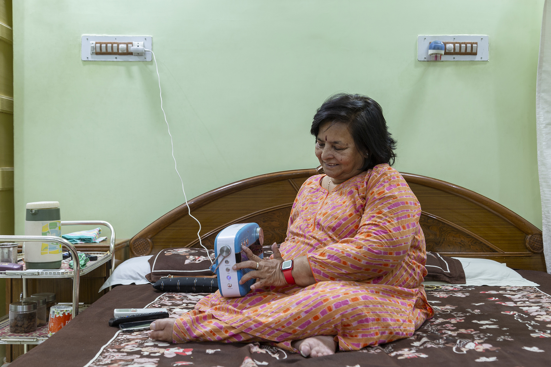 Kusumlata wearing a salwar-kameez with a pale multi-colour pattern sits crosslegged on her bed with a blue Saregama Carvaan (portable digital music player) on her lap. She is smiling as she pushes a button on the player, which has a long white wire that is plugged into a socket of an electrical switchboard on the wall.