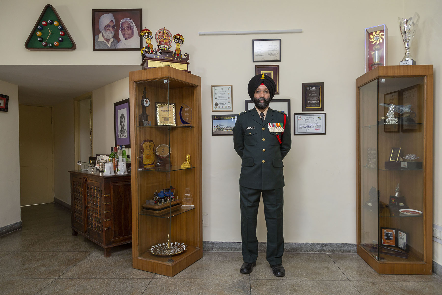 DP standing in military uniform between two glass cabinets filled with trophies, with framed certificates on the wall behind him. High up to the left is a framed photo of an elderly couple.