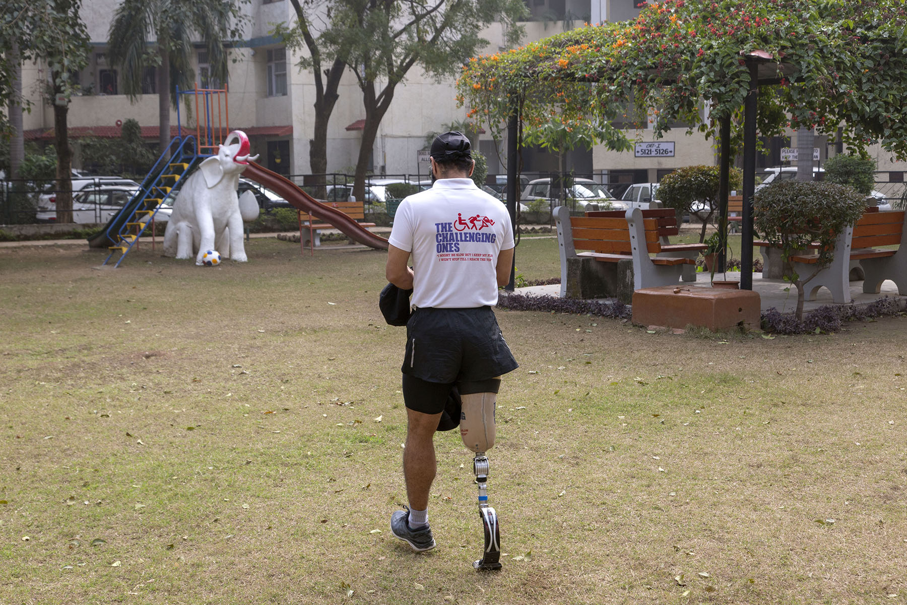 """DP wearing his blade, black shorts and white T-shirt that says """"The Challenging Ones"""" is walking away from us in a park. Ahead of him is a children's slide fronted by the statue of a white elephant with its trunk raised."""