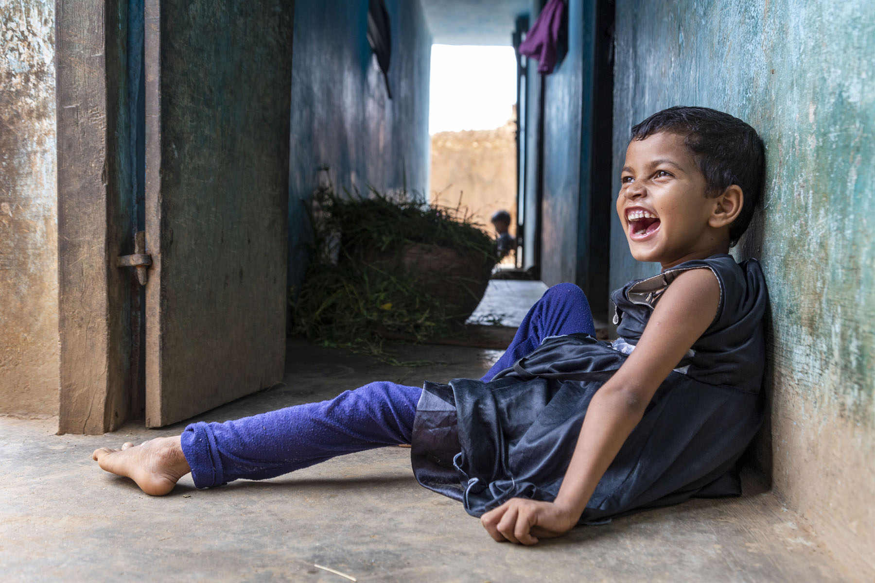 Manisha Kumari Mahto (8) dressed in an indigo churidar and navy blue frock sits on the floor, leaning against a wall painted blue. She has close-cropped hair and her mouth is wide open in laughter.  She has stretched out her left leg and her right knee is bent and raised up.