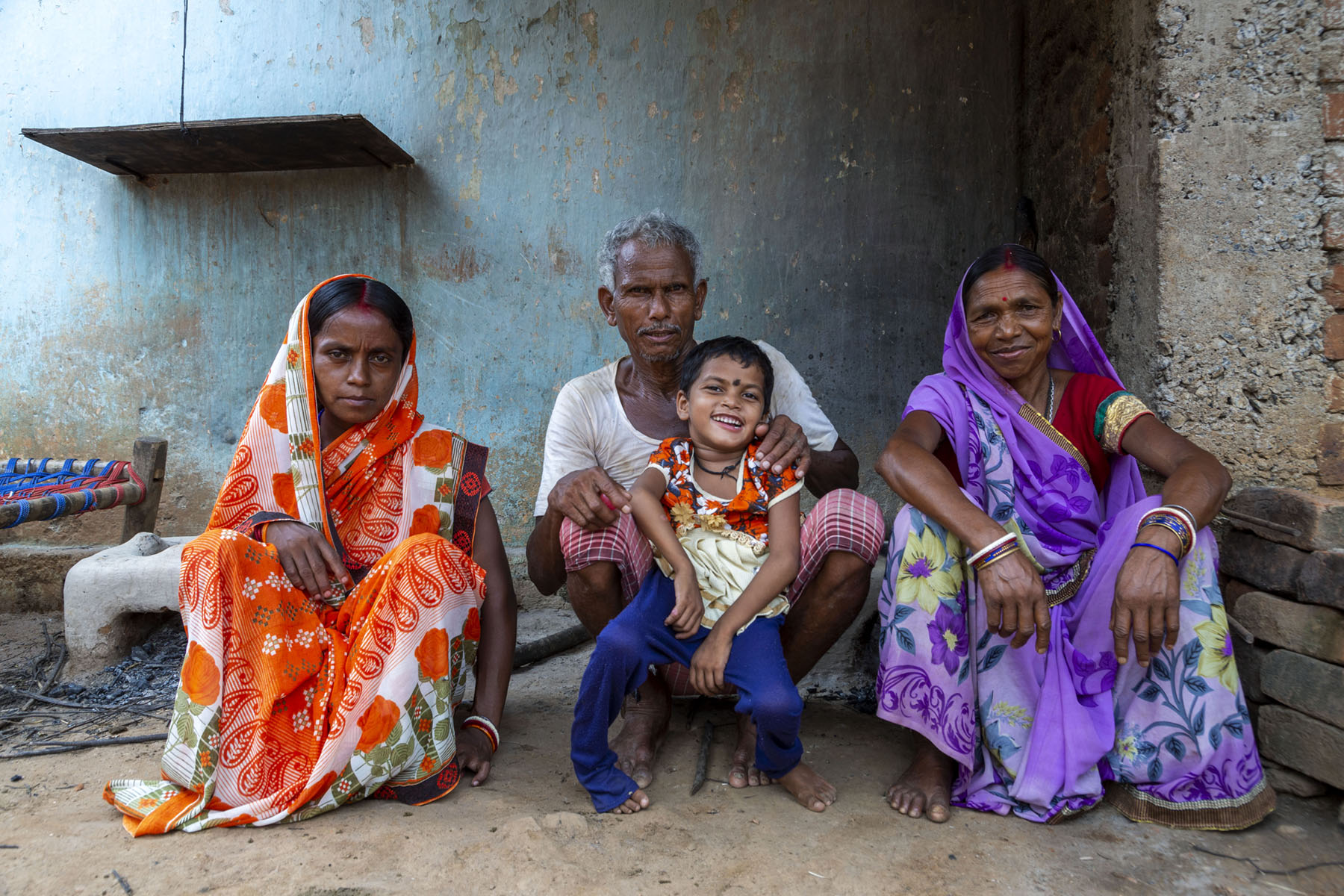 Squatting on the floor in a row and posing for the camera are — from left to right — Manisha's mother Savita Devi (29), grandfather Kailash Mahto (55) with Manisha in his lap, and her grandmother Minni Devi (50). Savita wears a sari in a mango design of bright orange on white. Her pallu is draped over her head. Kailash is in a banian and checked lungi. Manisha in her flower print dress and churidar, with a prominent black bindi on her forehead, nestles in her grandfather's lap, smiling broadly. Minni Devi wears a bright violet sari in a print of violet and white flowers with blue leaves.