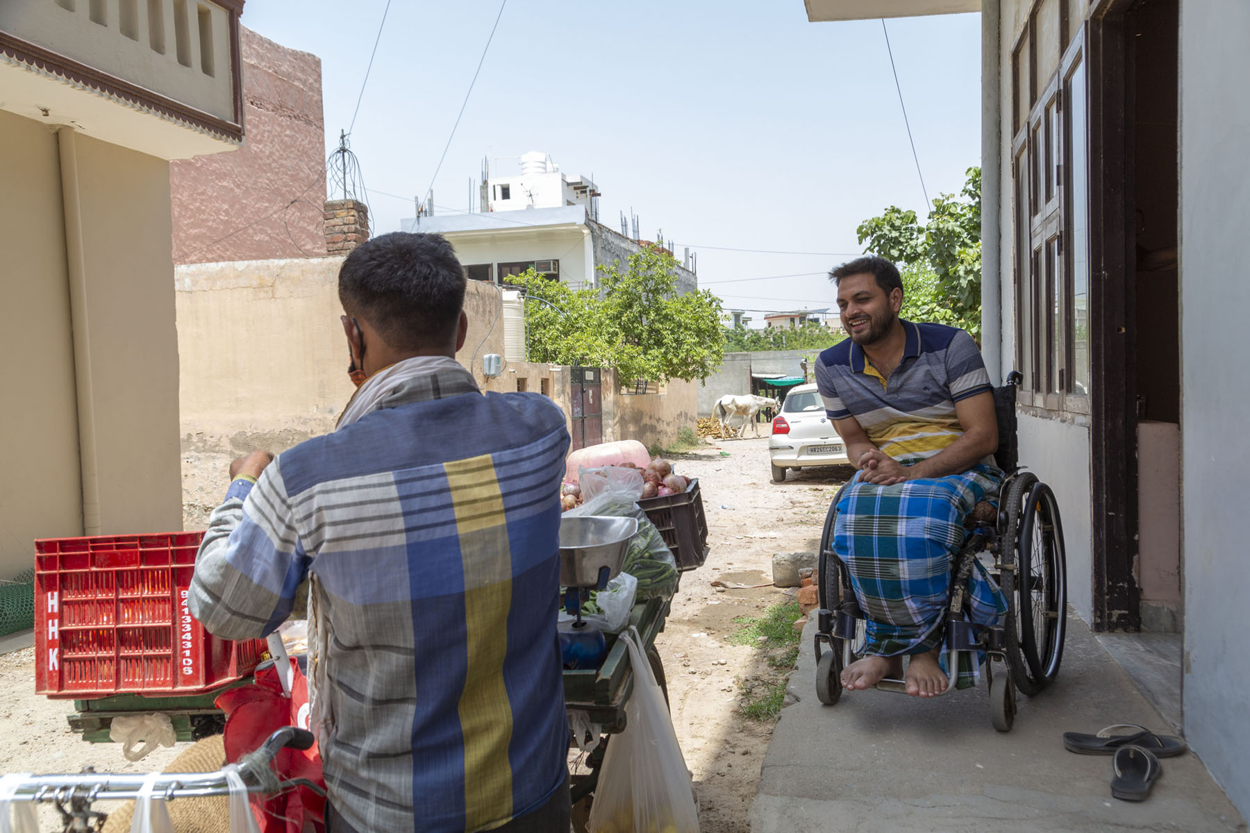 Shams sits in his wheelchair just outside his front door which opens out to a kachcha road. He wears a blue and grey checked lungi and a T-shirt with horizontal stripes in three different shades of grey. A vegetable bicycle cart is parked just outside the door and Shams is smiling and saying something to the vendor. The vendor has his back to us and he wears a full-sleeve cotton shirt with an indigo-blue and mustard-yellow design.