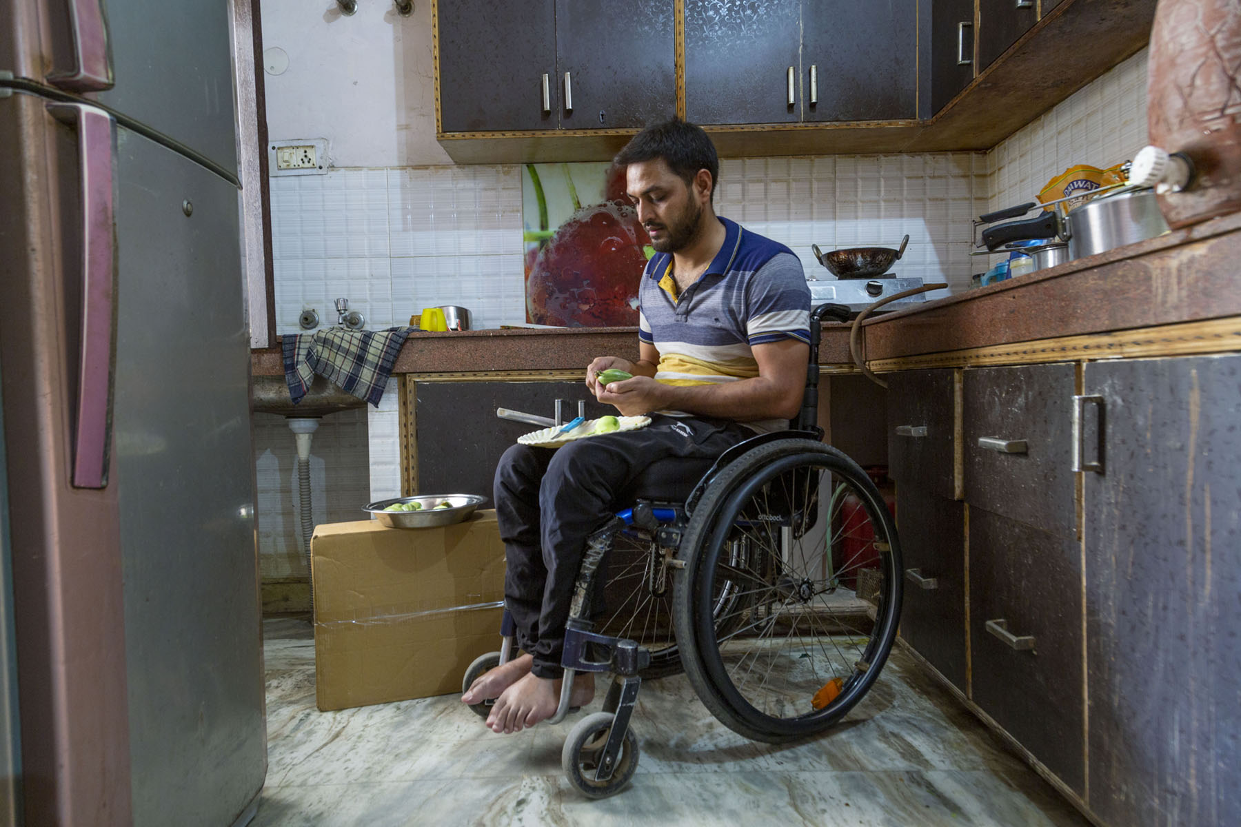 Shams sits in his wheelchair in a corner of his kitchen. A white plate is balanced on his lap. He is cutting a green vegetable with a small knife. The kitchen wall has white tiles. The platform is made of brown marble and there are matching brown kitchen cabinets and drawers. On the platform are some vessels and a gas stove with a kadai on the burner.