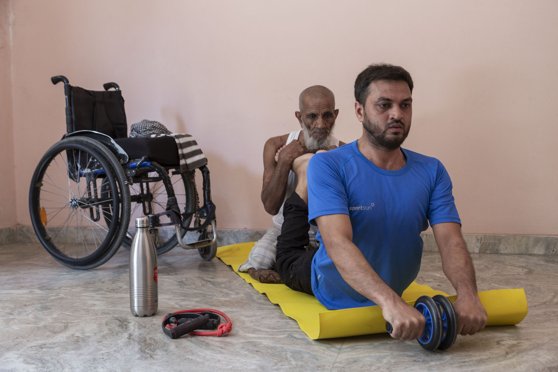 Mohammad Shams Aalam Shaikh is exercising on a yellow yoga mat, lying on his stomach. Wearing a blue T-shirt and black track pants, he has raised his head and chest. Both arms are extended. His hands, holding a roller, rest on the ground. Both knees are bent backwards and his 90-year-old father is sitting down behind him and holding up his feet. On the ground to their left are a steel flask and a wheelchair.