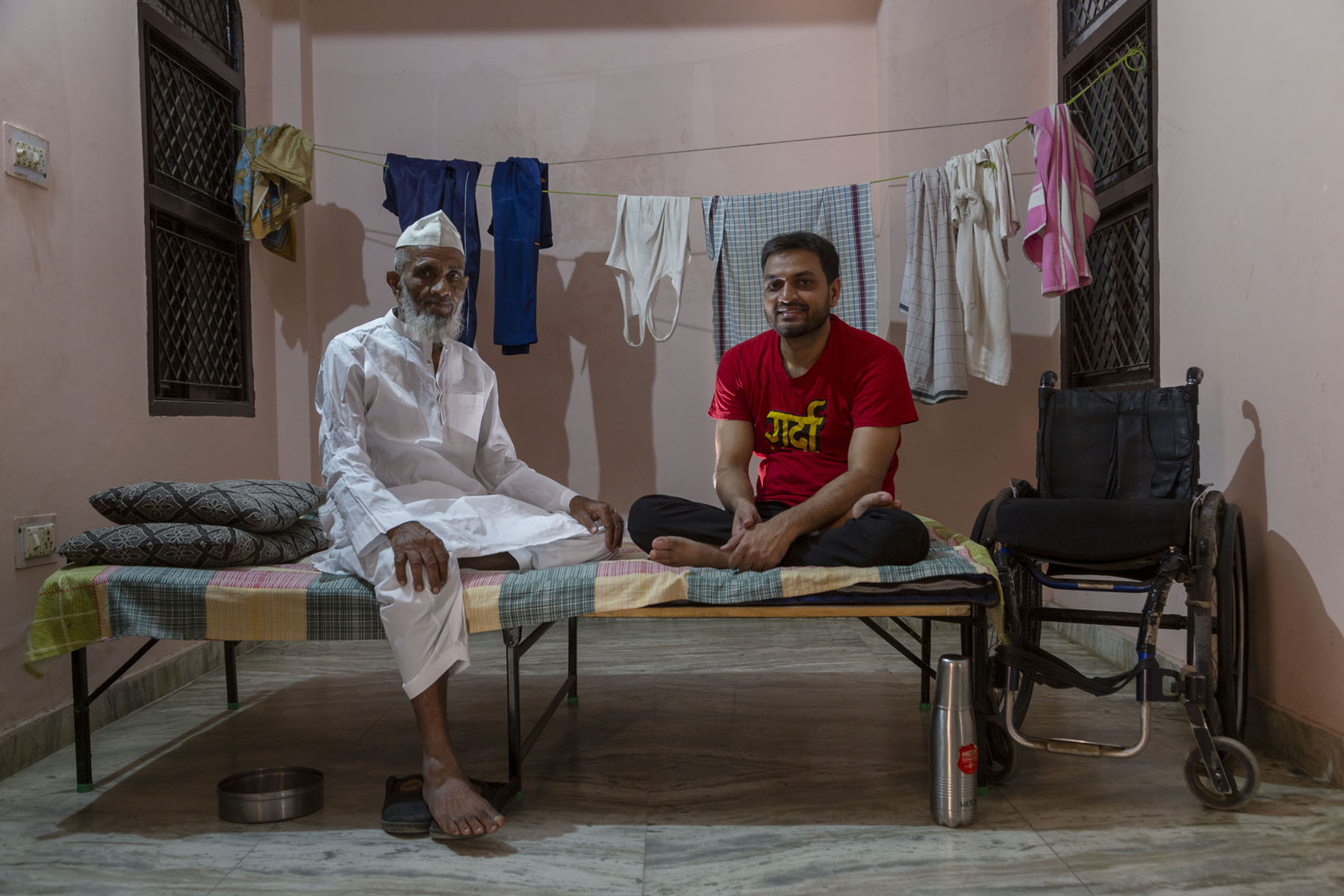Shams is smiling as he sits cross legged on his bed next to his father Mohammad Nasir (90). Nasir has a full white beard and wears a white kurta-pyjama and white cap. He has one leg folded at the knee resting on the bed, and the other leg dangling to the ground. Shams wears a red T-shirt and black pants.