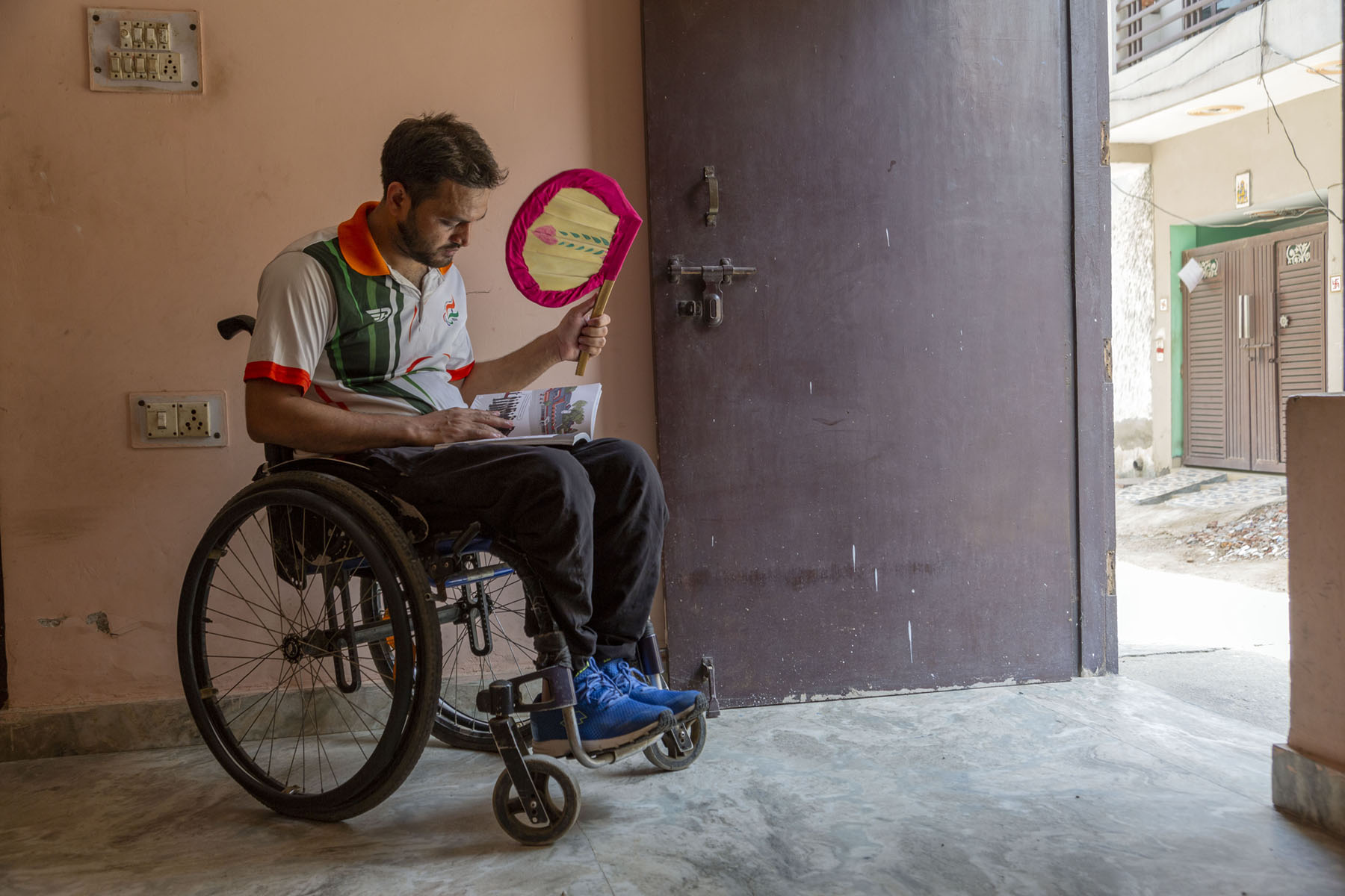 Shams sits in his wheelchair in the front room of his house. He has a close-cropped beard and moustache. Light falls on him from the open front door. In one hand he holds a book which he is reading and in the other, a palm-leaf hand fan with a wooden handle. He wears a white T-shirt with an orange collar, dark brown trousers and blue sneakers.