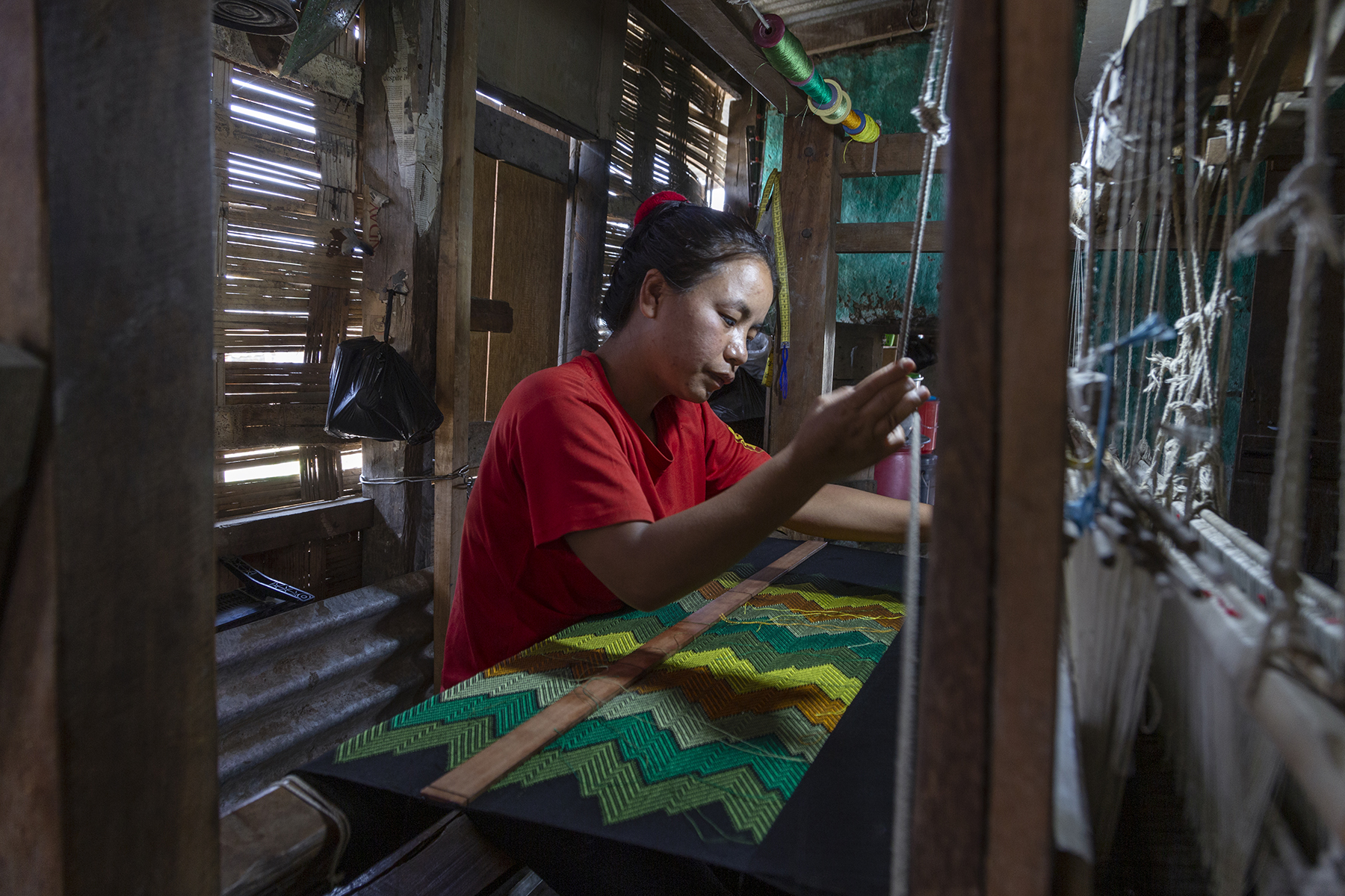 Side shot of Ngaihnem in a red T-shirt, standing in a narrow space, weaving on a loom. The fabric before her has a zigzag pattern of alternating bands of yellow, orange, and three shades of green. Her left hand is outstretched and right hand is raised to hold a vertical, thick, white cord.