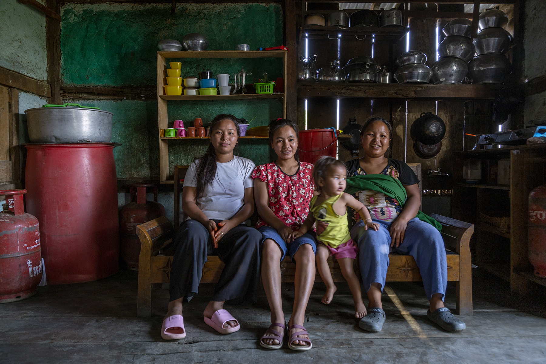 Ngaihnem sits with her sisters and nephew on a wooden divan. From left to right: Niang Liankim (28) in white T-shirt and black pants, Ngaihnem in blue shorts and red top with small white flowers, and Chingnunmoi (25) with light blue pants and a folded green shawl draped crosswise on her black T-shirt. Chingnunmoi's son Moisuankim (1.3 years) sits between her and Ngaihnem wearing a yellow banian and pink shorts. To the left are a gas cylinder and a huge red drum. Behind them are wooden shelves filled with steel vessels, porcelain cups and plastic containers.