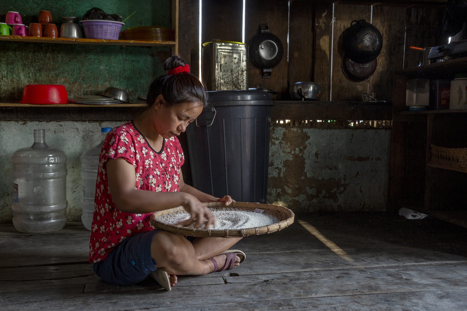 Ngaihnem, wearing a short-sleeved, U-neck top with small white flowers on a red background, sits cross-legged on the wooden kitchen floor. A large circular tray made of bamboo cane is placed on her lap.  It contains white raw rice which she is swirling with her hand. Behind her are porcelain cups and steel plates on two wooden shelves; a black plastic water drum; and pans and woks hanging from hooks on the wall.