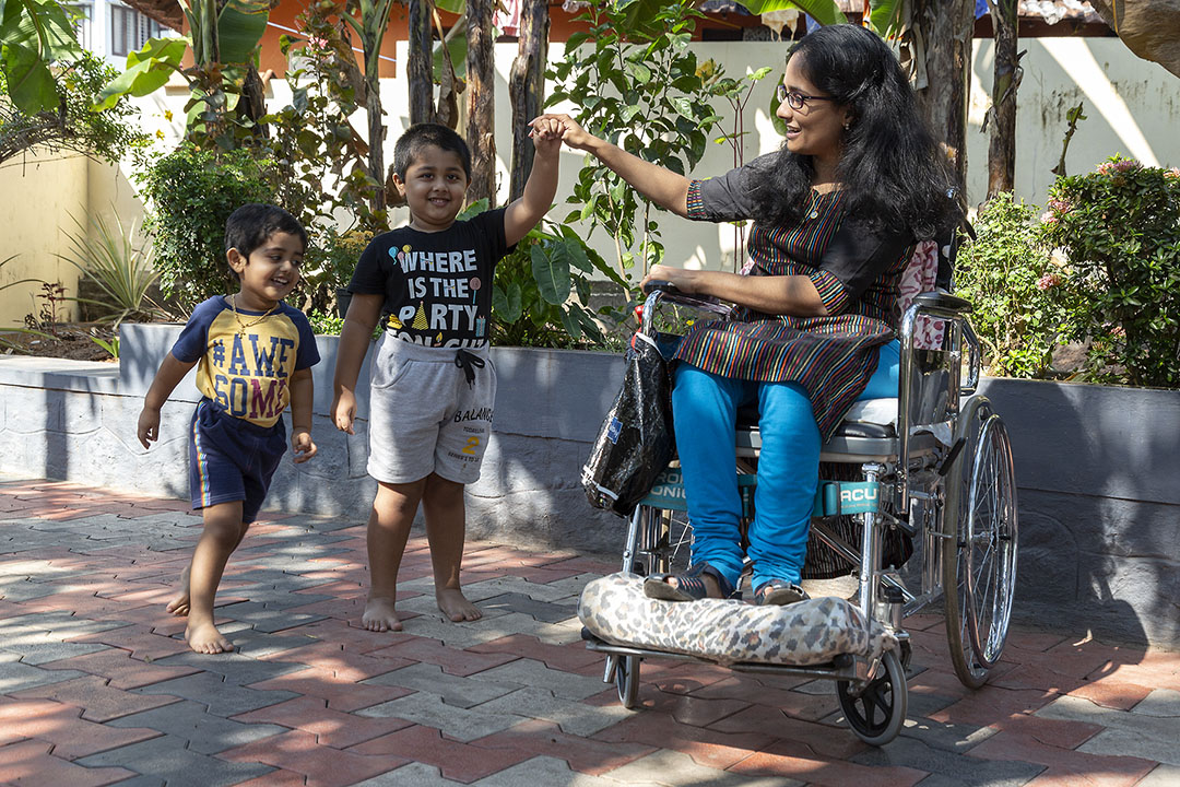 """Nincy Mariam Mondly outside her house with her nephews Liam Jo Dany, 3, and Louie Mondly Dany, 2, who wear T-shirts tucked into shorts. All three are grinning. Nincy, with shoulder-length open hair, wearing black-frame spectacles, kameez with a multi-coloured pin-stripe pattern and blue churidar, sits in her manual wheelchair with her feet on a cushion placed on the footrest. The ground is paved and there is a bed of plants behind her. She is holding up Liam's left hand with her right in an inverted V. Louie stands next to his brother. Liam's T-shirt says """"WHERE IS THE PARTY"""" and Louie's, """"AWESOME""""."""