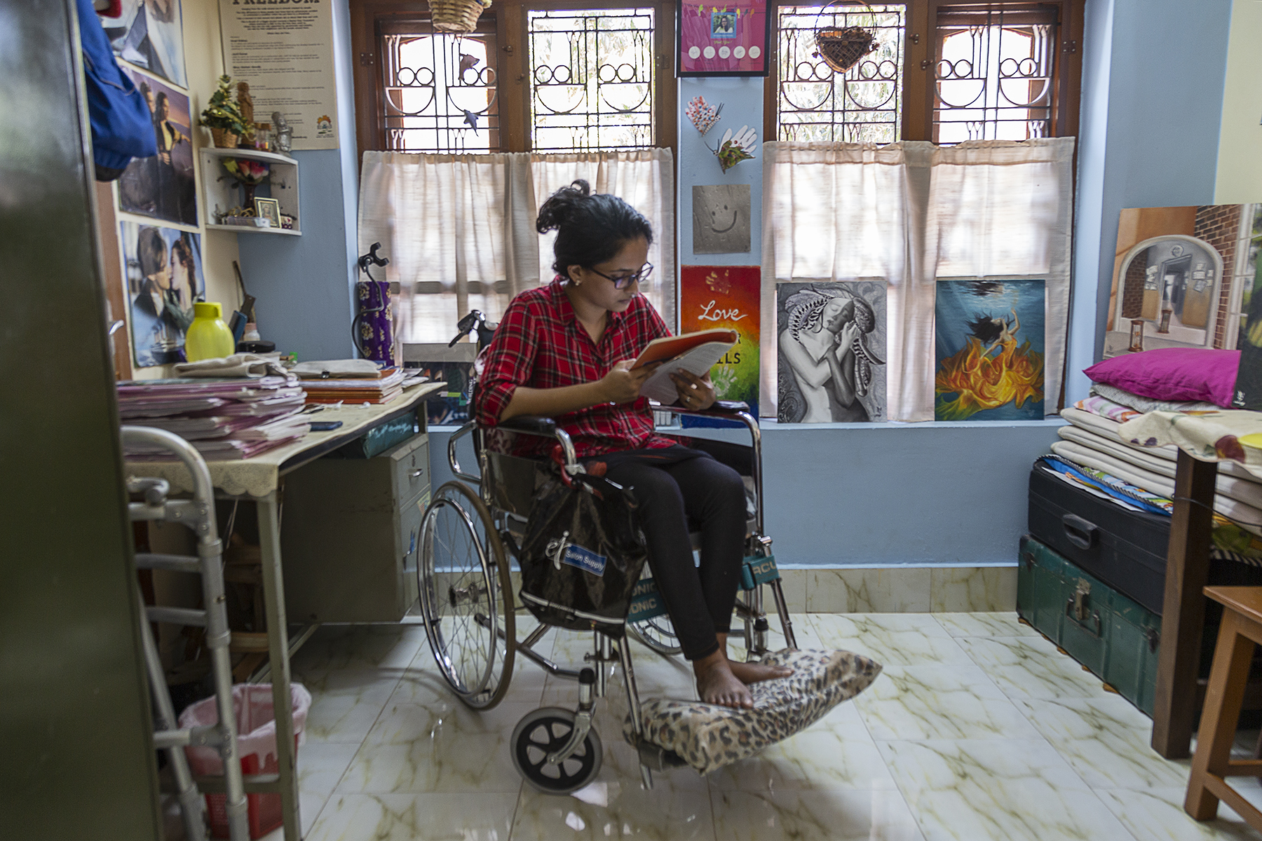 Nincy in her wheelchair in her room is reading a book. Her hair is tied back and she wears a red shirt with big black-and-white checks, the sleeves folded up to the elbow, and black skintight jeans. There are two adjacent windows behind her with grills and half-curtains. Two of her paintings are propped up on a window sill. In the far right corner a large black metal trunk sits on top of a similar green one. In the far left corner is a steel table with drawers, piled high with sketchpads.