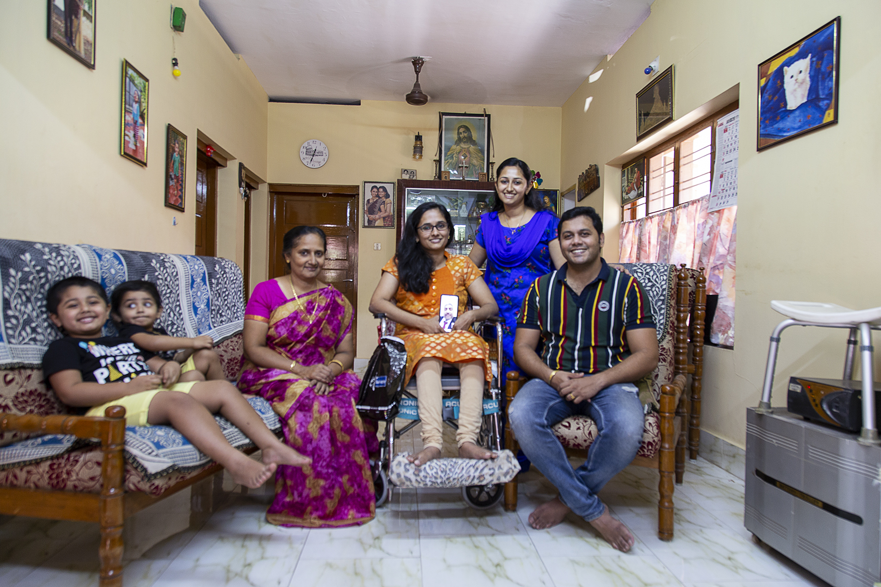 Nincy and family pose in the living room. Nincy in orange kameez and beige churidar is in the centre of the frame, in her wheelchair, holding up her phone screen which shows a photo of her father Mondly Mathew Oommen, 60. Liam and Louie in shorts and T-shirts sit on a double sofa in the near left corner. Lena in a magenta sari sits to the left of Nincy, and Nimmy in a royal blue salwar-kameez stands to the right. Nimmy's husband Dany John Selvan, 33, sits at the extreme right, dressed in light blue jeans and black T-shirt with yellow, white and maroon vertical stripes.