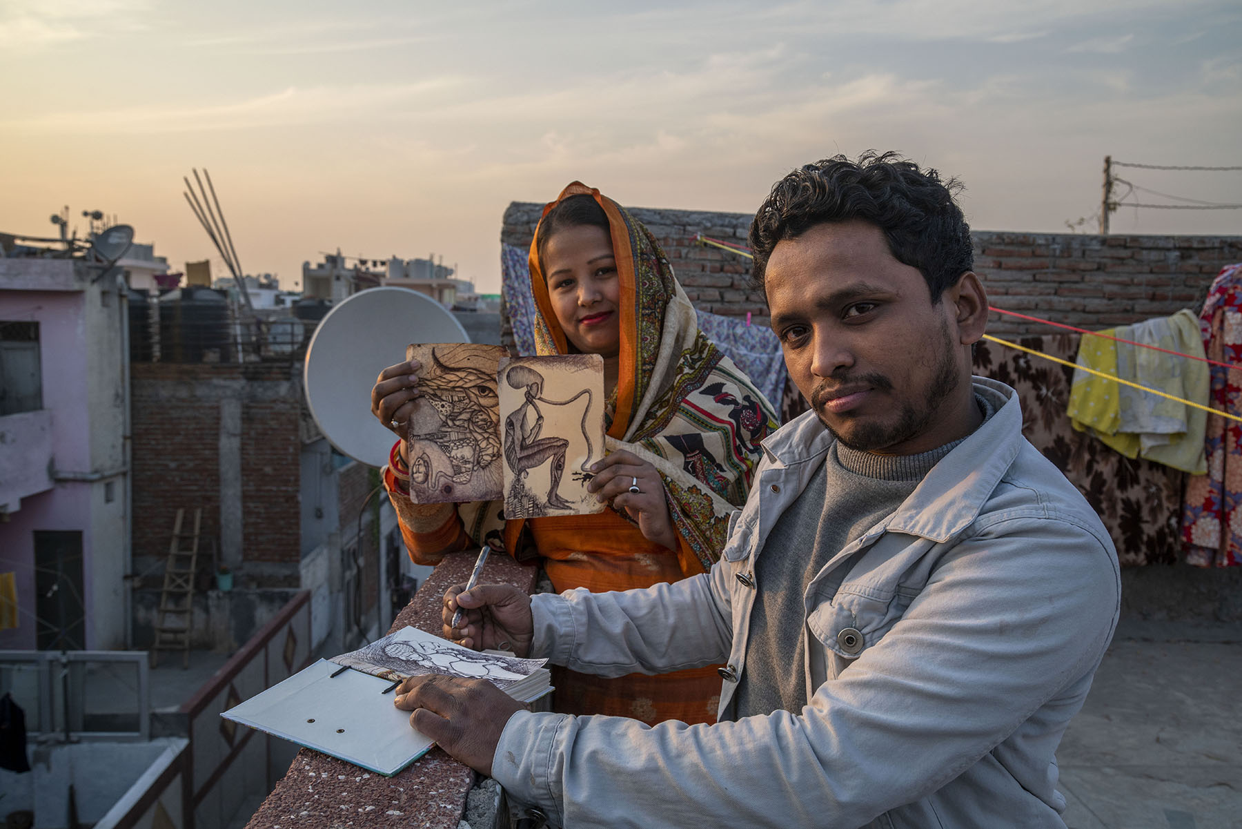Niyaz and his wife Meenu are standing on an open terrace, leaning sideways against a parapet. Niyaz has placed an open sketchbook on top of the wall and holds a pen. Meenu is behind him, holding up two of his black-and-white sketches.