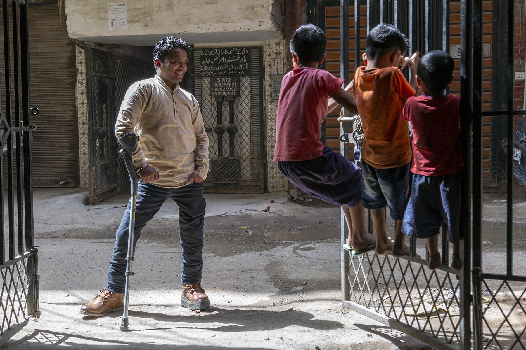 Niyaz wearing a beige kurti and blue jeans stands on the road outside the open front gates of a house. He is leaning on his crutch and smiling at three little boys in shorts and T-shirts who are swinging on one of the gates. They have their backs to us as they stand in a row, clinging to the vertical bars of the gate, their feet placed on one of the higher horizontal bars.