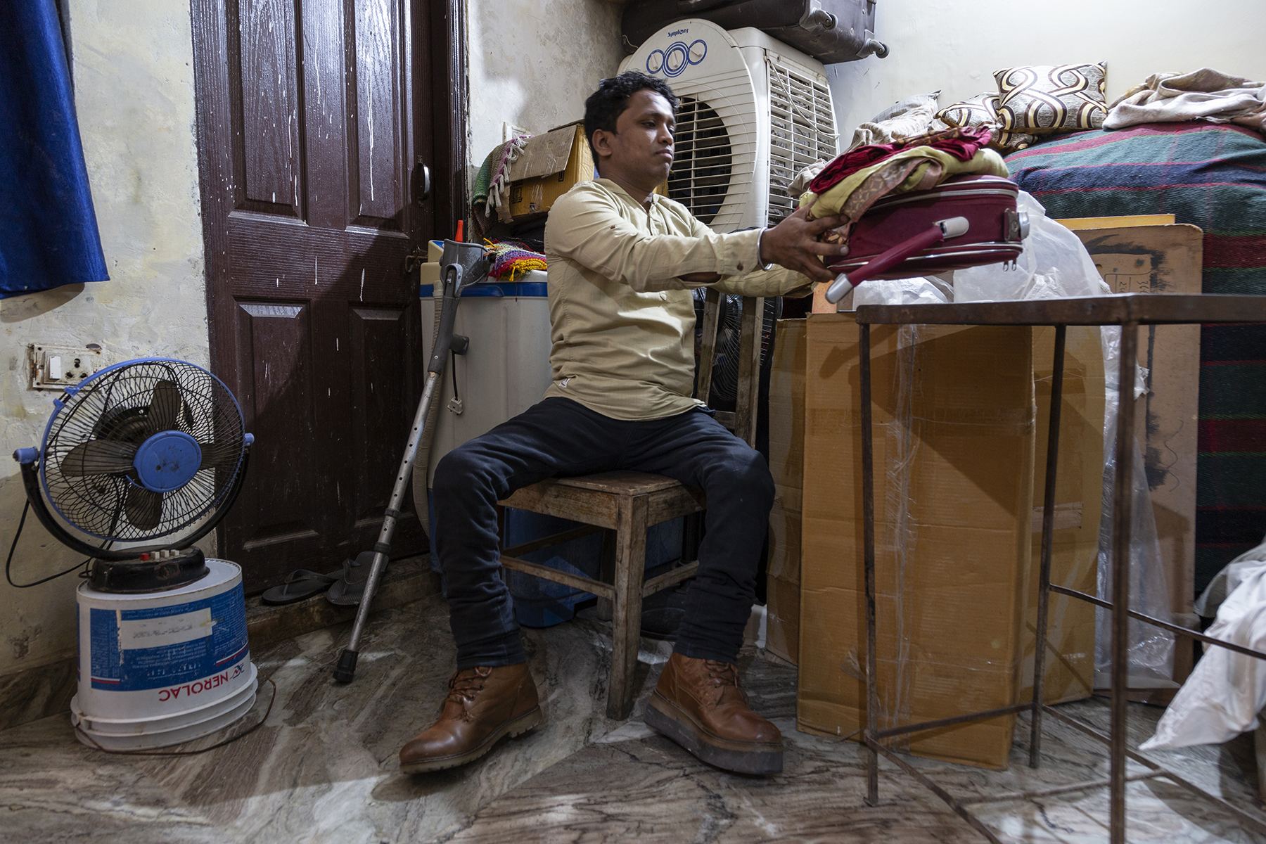 Niyaz sits in a room on a wooden chair facing us. He is leaning to the right to place a bundle of clothes on a metal table. His crutch is propped up to the left. In the left bottom corner, a blue table fan is placed on top of an upside down white plastic bucket.