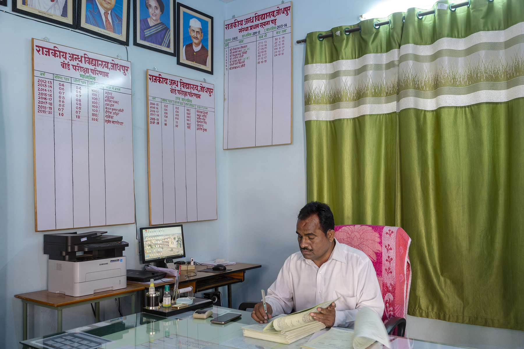 Prakash Chand, wearing a white full-sleeved shirt, sits in his office, holding a pen upright in a thick, open book. He sits at a long, glass-topped table and a green silken curtain covers the large window behind him. To the left is a long, narrow table with a printer and a computer. Three large white boards hang on the wall with letters painted in red in Hindi. The heading says Rajkeeya Andha Vidyalaya, Jodhpur. Two of the boards list the board exam results for different years and the names of the top rankers. The third board has the names of former principals and their term of office; the last name is that of the current principal, Prakash Chand, who took charge on 5-10-2019.