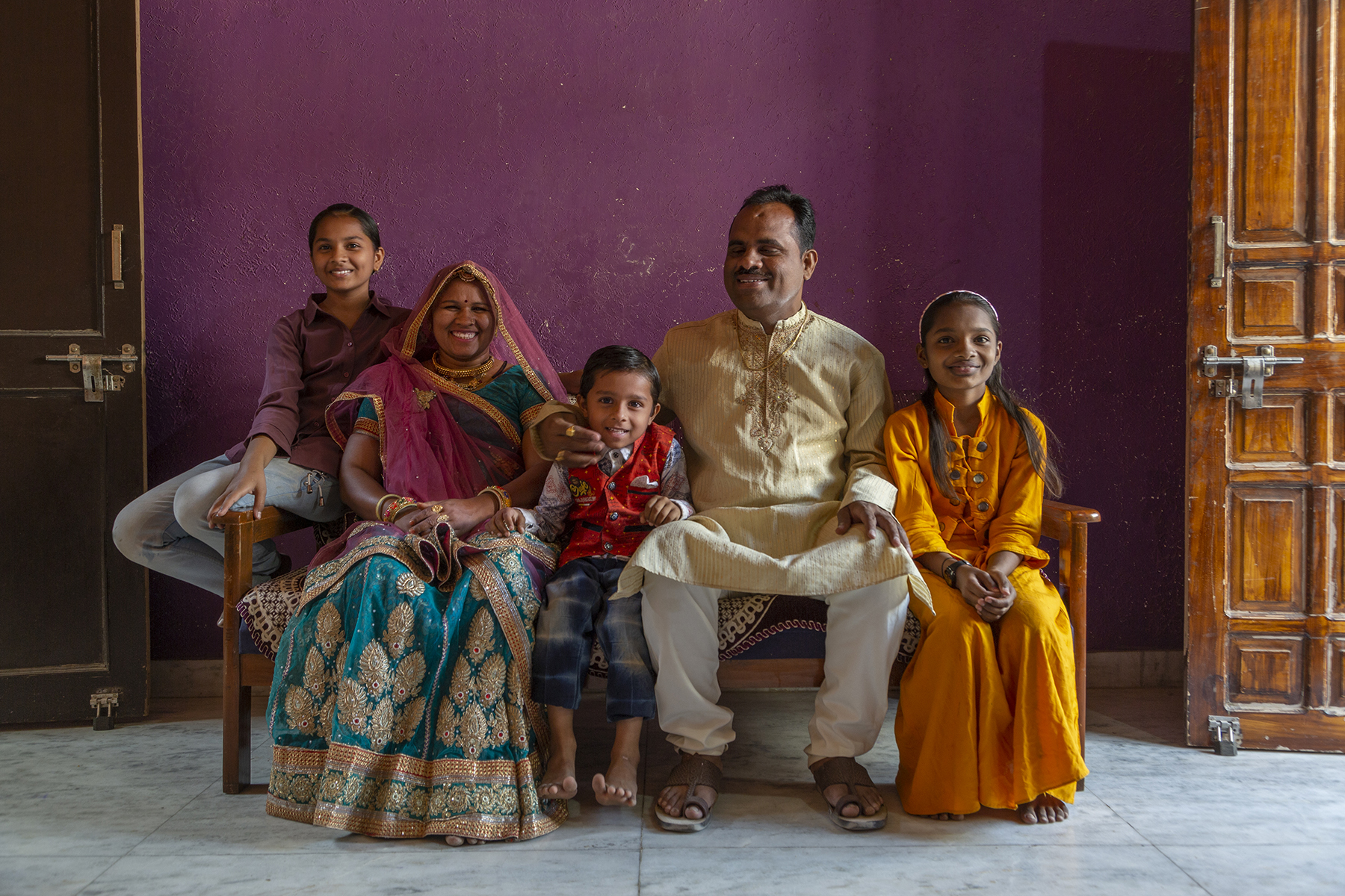 Prakash Chand and his family pose on a sofa, smiling broadly. From left to right, daughter Ruchika (12), wife Kavita (37), son Piyush (5), Prakash, and daughter Nidhi (10). Ruchika wears a chocolate-brown full-sleeved shirt and light blue jeans. Kavita wears a dark green traditional lehenga-choli with zari embroidery paired with a zari-edged orange dupatta draped over her head. Piyush wears calf-length shorts and shirt with orange vest. Prakash wears a beige kurta with brown embroidery at the neck and white pyjamas. Nidhi is in a plain orange full-sleeved top and matching lehenga.