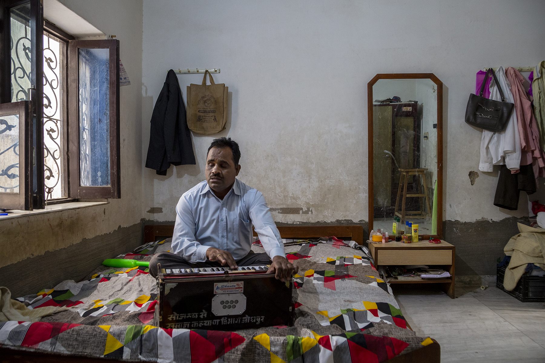 Prakash Chand sits cross-legged on a double bed, playing the harmonium. The bed is covered with a multi-coloured sheet. There is a window with open glass panes to the left, a leather bag and a coat hanging from hooks on the wall behind him, and a full-length mirror and dresser to the right.