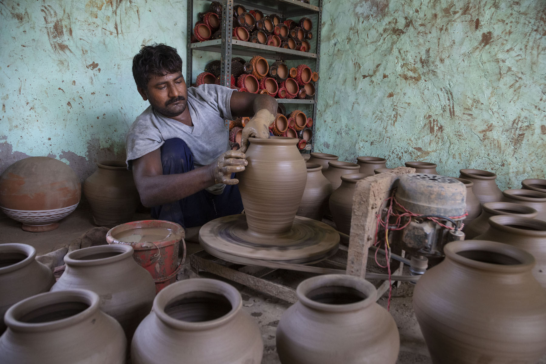 Ramotar (36), wearing grey T-shirt and black trousers, is squatting in front of the potter's wheel, shaping a clay pot with both hands. He has a moustache and short, wavy black hair. He is surrounded by around 15 unfinished water pots that have not yet been dried and baked. A metal rack behind him is stacked with three shelves of finished diyas (clay lamps).