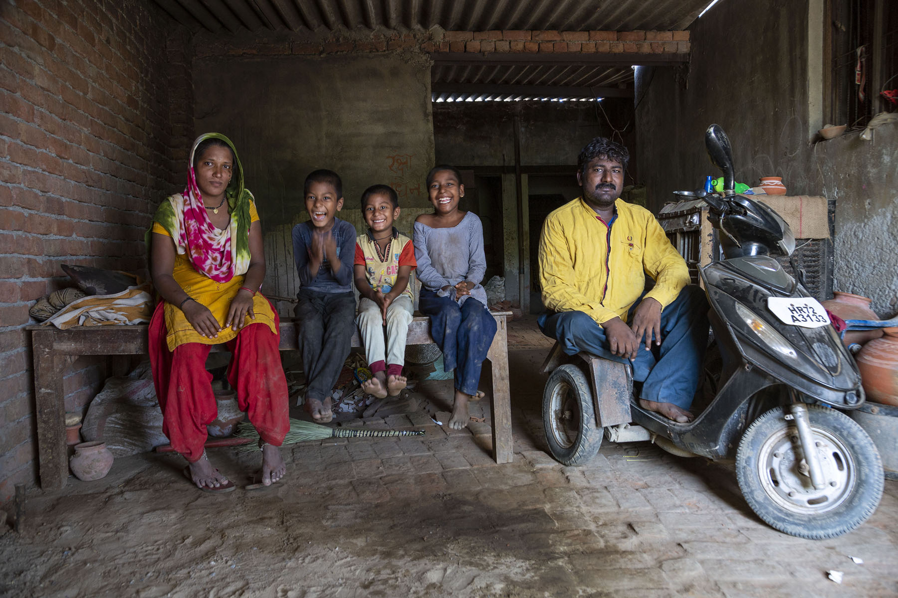 Ramotar sits in a black three-wheeled scooter modified for the disabled. He wears a yellow long-sleeved shirt and blackish-blue pants. To the left, his family sits in a row on a bare wooden cot. From left to right: his wife Sonya (27), and their children Manish, Prerna and Ekta. Sonya wears a red salwar, yellow kameez and dupatta with a red, green and white print. She has draped the dupatta over her head and shoulders. Manish wears dark brown pants and a tight, full-sleeved T-shirt. Prerna wears light-coloured pants and short-sleeved T-shirt. Ekta wears a full-sleeved long, light violet top and dark blue pants. All three children are laughing.