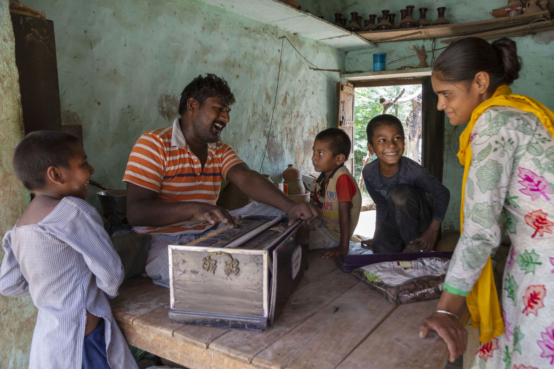 Ramotar wearing an orange and white striped T-shirt is sitting on the left edge of a wooden platform, singing and playing the harmonium. Opposite him stands his niece Chanchal in a printed salwar kameez and yellow dupatta looking at him with a half-smile. Sitting on the far edge of the platform are Ramotar's son Manish Kumar (6) and daughter Prerna (5). Manish is smiling broadly at Chanchal while Prerna is staring at Ramotar. Standing on this side of the platform is Ramotar's older daughter Ekta Rani (8), smiling at Manish. All the children have close-cropped hair.