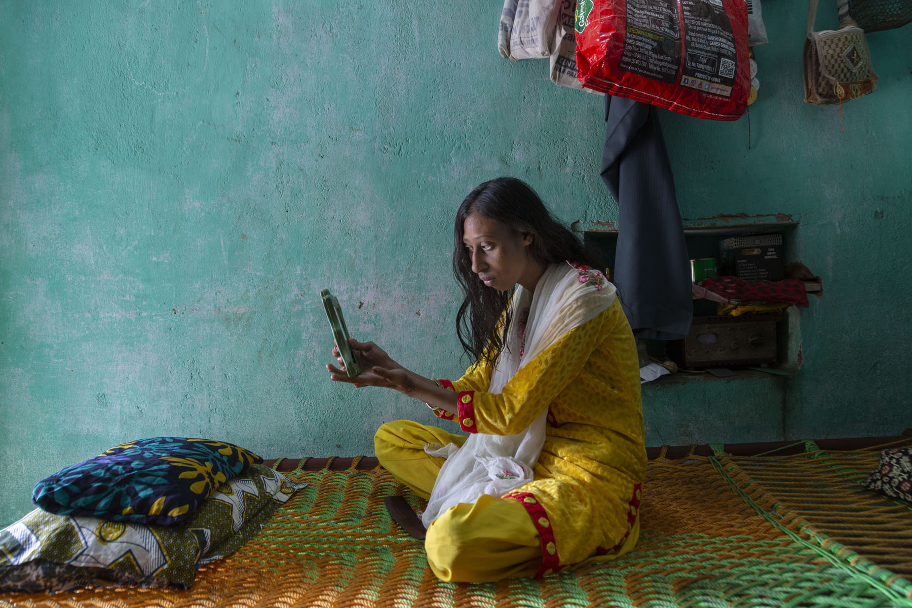 Roji sits cross-legged on a charpoy in a room with blue walls. Dressed in yellow salwar-kameez and white dupatta, she is looking into a small mirror that she holds with both hands. Her hair is open and falls around her back and shoulders. The charpoy is woven with orange and green plastic rope. It has two pillows with multi-coloured covers.