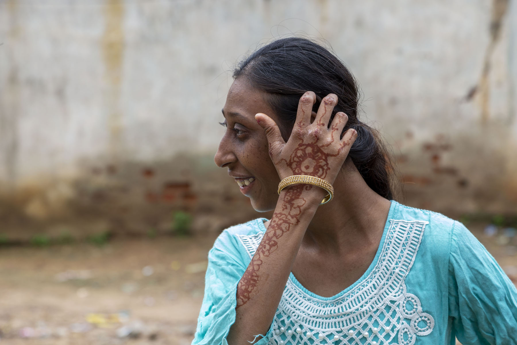 Close-up of Roji Nisha (21) with black hair tied back and wearing a sky blue top with white embroidery on the front. She has turned her head to her right and is smiling. She has raised her right hand up to touch the left side of her head. A decorative mehendi pattern runs all along the back of her arm, hand and fingers. A broad, gold-coloured bangle adorns her wrist.