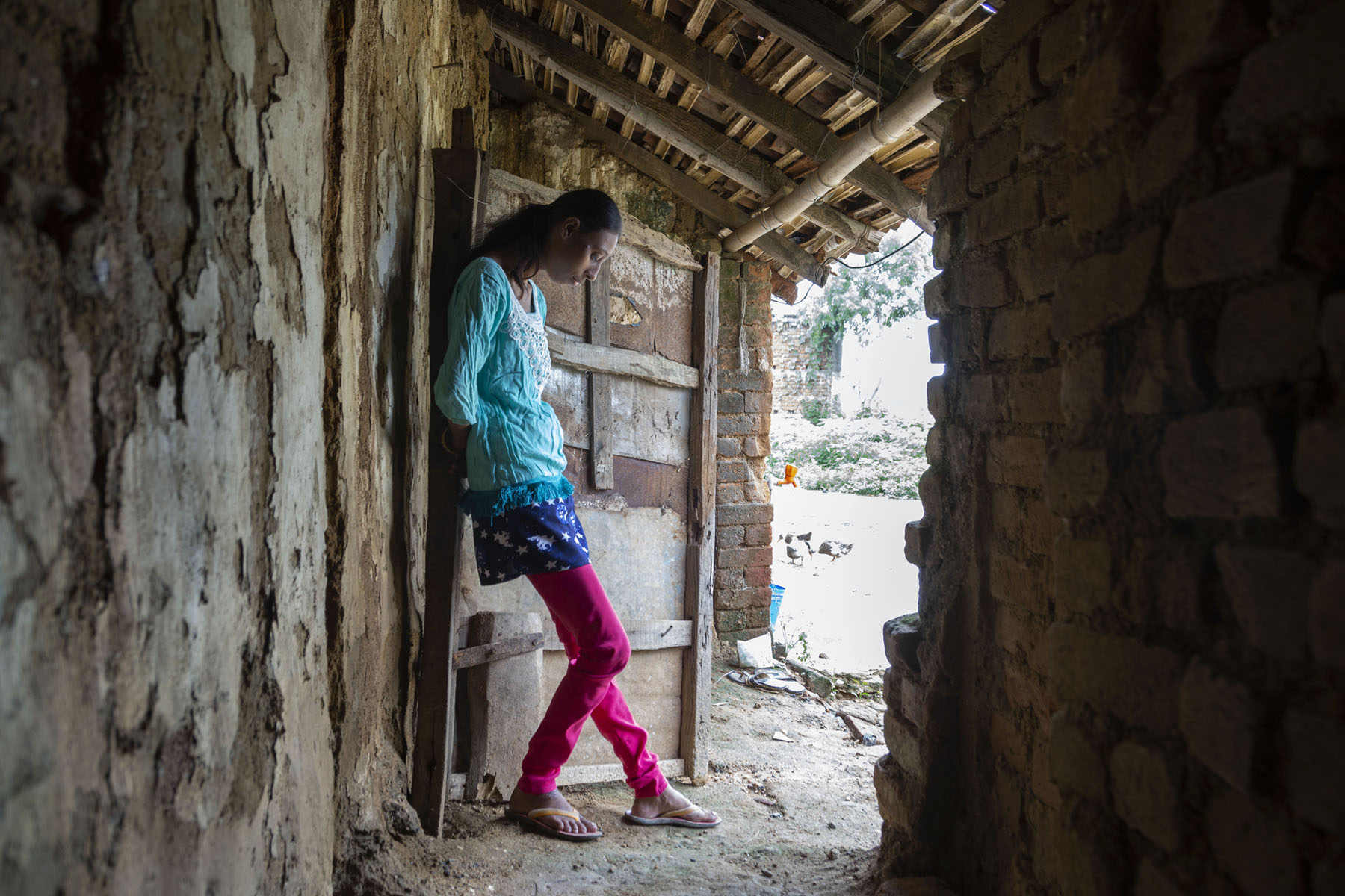 Roji is standing with hands behind her back, leaning against a wooden door that looks out onto the street. She is looking down at her feet wearing in slippers with yellow straps. She wears a magenta churidar and blue kameez.