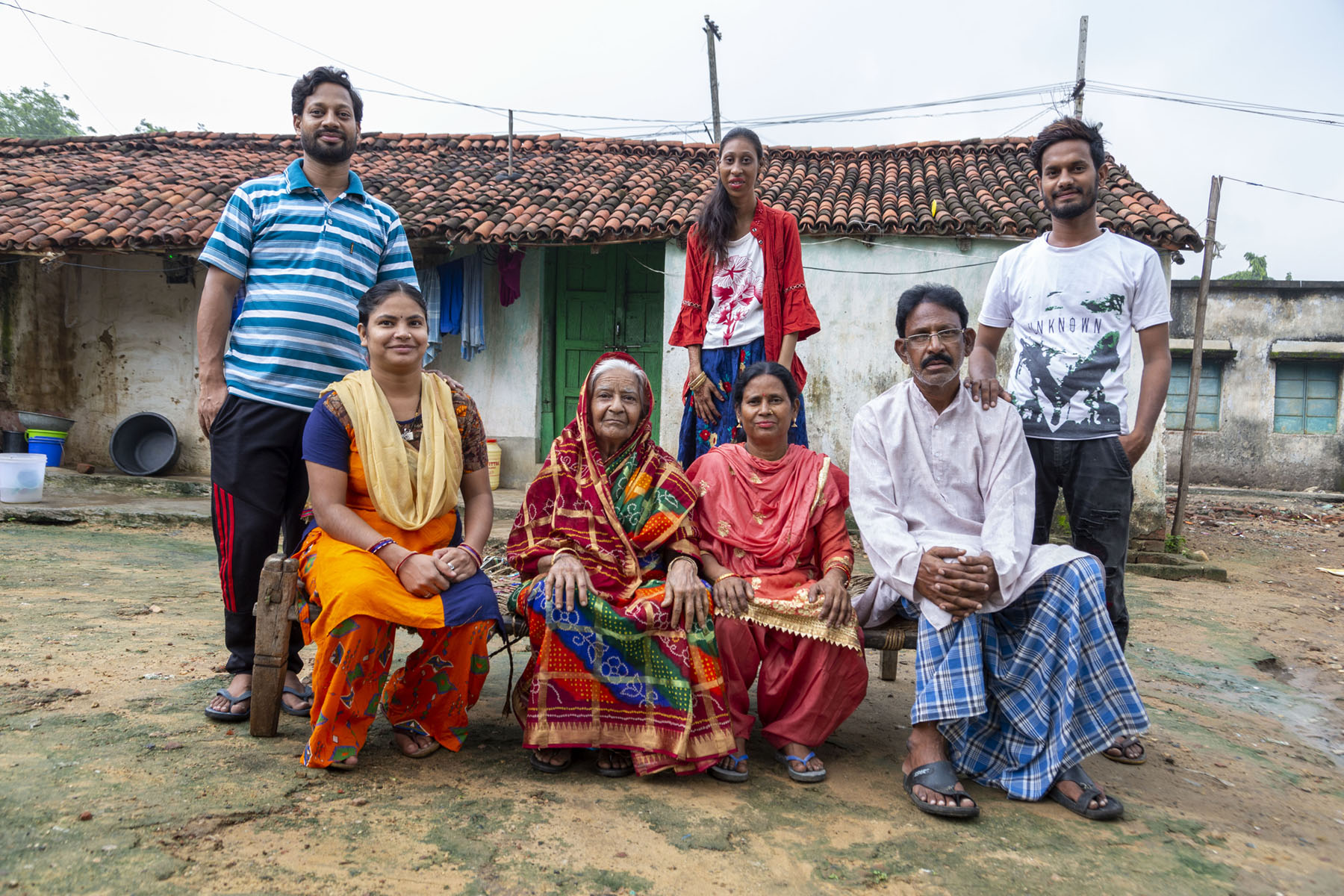Roji poses with her family. Sitting on a wooden bench from left to right: Sister-in-law Suraiya Parween (24), grandmother Salma Bibi, mother Mariyam Nisha (54) and father Anwar Saudagar (60). Behind them, Roji stands in the centre between her brothers Mohammed Jabed (25) at extreme left and Mohammed Jahid (20) at the extreme right. Suraiya wears an orange and violet pattern salwar kameez and cream dupatta. Salma wears a sari with a red, green and violet design; the pallu is draped over her white hair. Mariyam is in a rose-red salwar-kameez. Anwar wears a blue and black checked lungi and a pinkish white kurta. Jabed is in a collar T-shirt with horizontal blue and white stripes and navy blue track pants. Rosi has on a front-open red shirt with bell-shaped three-fourth sleeves worn over a short, white T-shirt with a red flower on the front. She wears a navy blue skirt decorated with red and yellow flowers. Jahid wears black trousers paired with a white T-shirt.