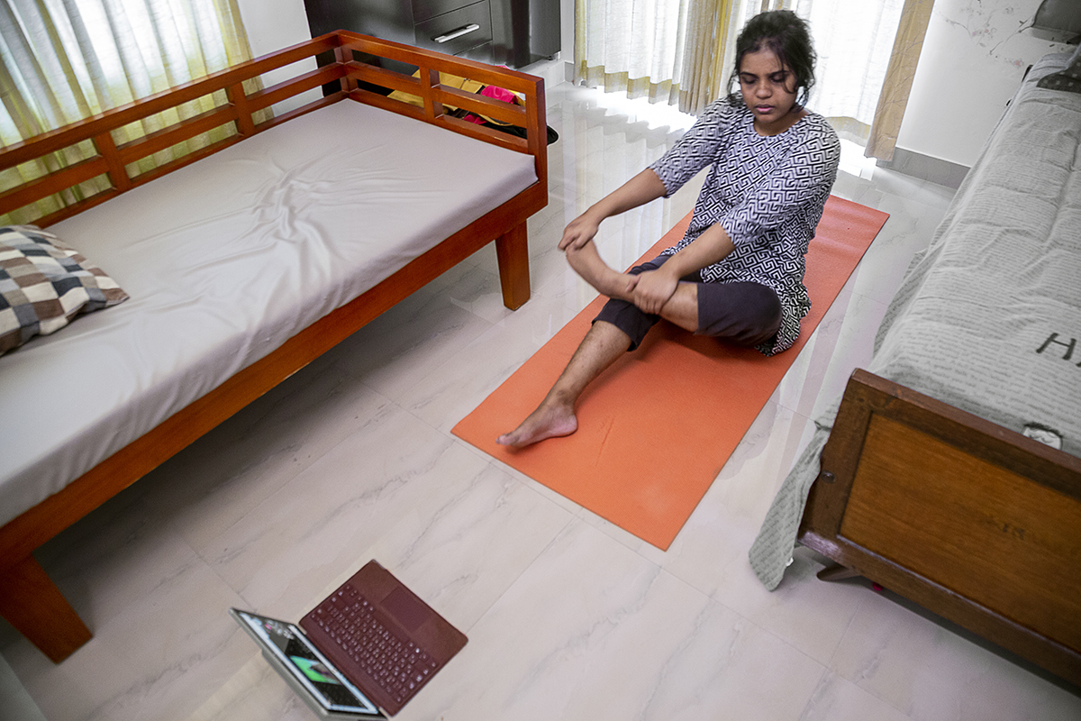 Overhead shot of Ruwaydah sitting on an orange yoga mat, right leg stretched, both hands holding her left leg folded at the knee. The mat is placed between two wooden cots with mattresses. To the front of the mat a few feet away is an open laptop.