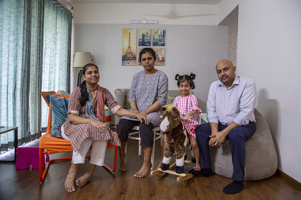 Ruwaydah and her family sit in a row in the living room. From left to right: Her mother Sulekha Raja, Ruwaydah, three-year-old sister Maryam, and father Mohammed Raja. Sulekha in a white salwar and kameez with a brown zigzag pattern sits in an orange chair. Ruwaydah in a long top with a black-and-white geometrical print and black calf-length pants sits on a white stool. Maryam in a pink-and-white checked dress sits on a brown-and-white rocking horse. Mohammed wearing navy blue trousers and pale blue full-sleeved shirt sits on a light-coloured bean bag. Framed paintings of the Eiffel Tower and other cityscapes hang on the wall behind them. To the left, sunlight shines faintly through blue drapes on a French window.
