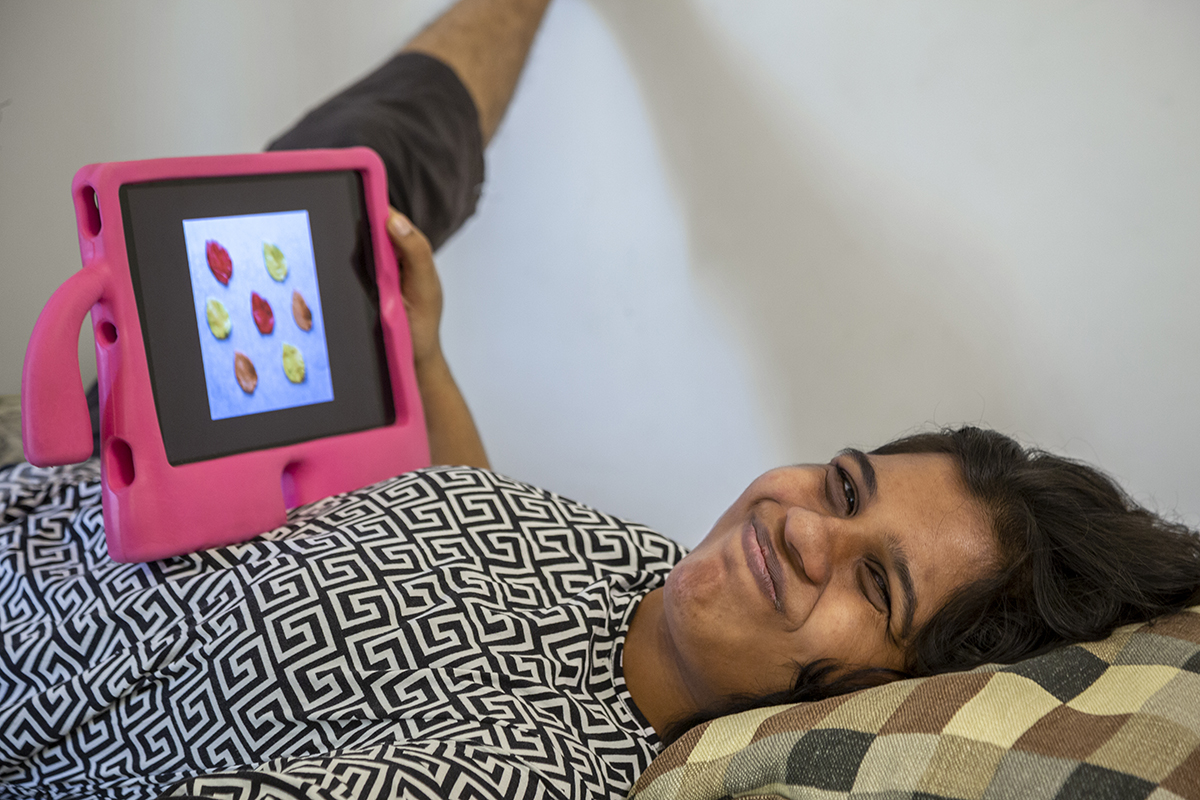 Ruwaydah Raja lies flat on a bed, smiling broadly, holding an iPad with a bright pink cover that rests on her chest.