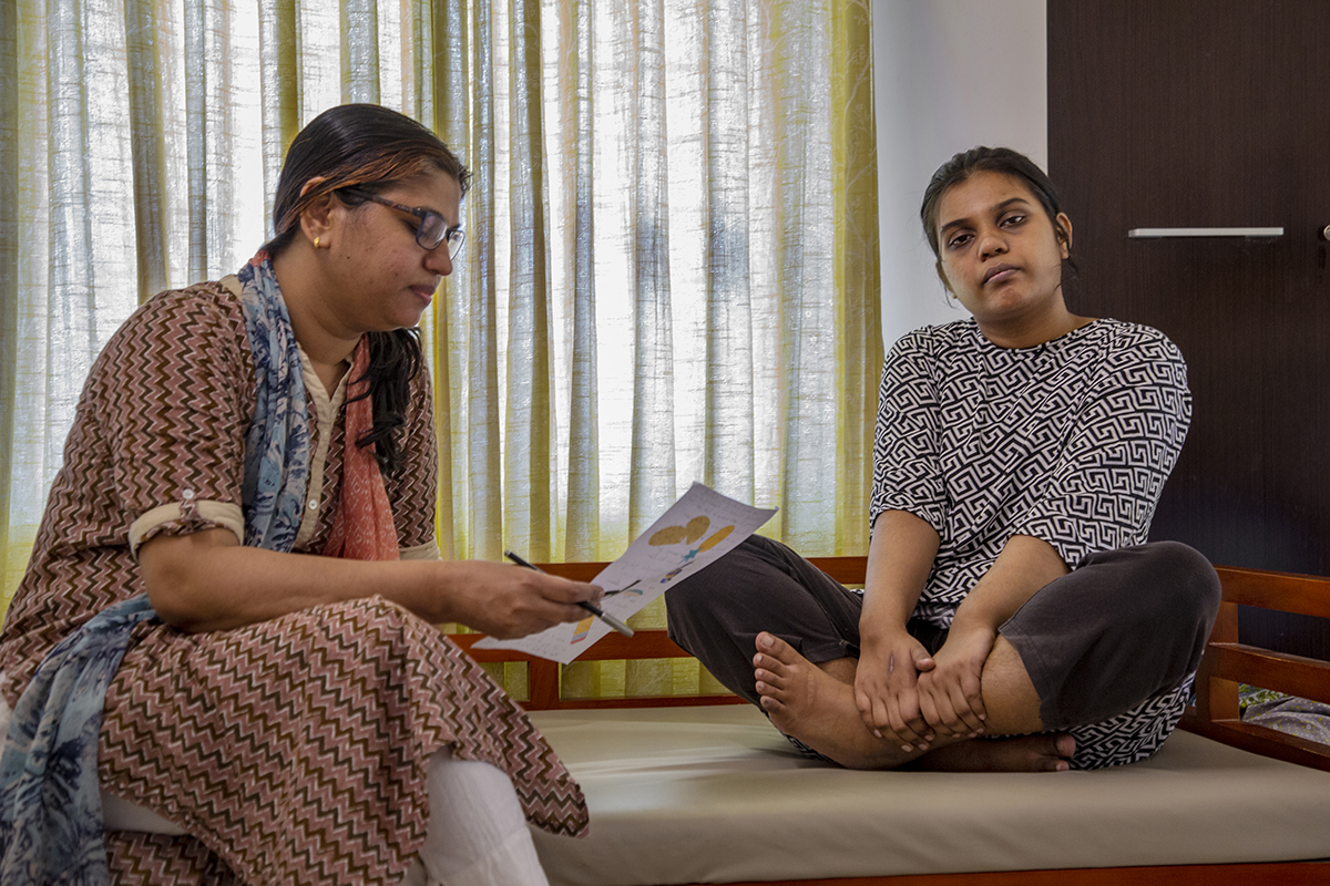 Ruwaydah and Sulekha are sitting on a bed. Ruwaydah sits cross-legged with both hands clutching her feet. Sulekha, wearing glasses, is holding a sheet of paper and a pen in her right hand. She is looking at the paper which has drawings on it.