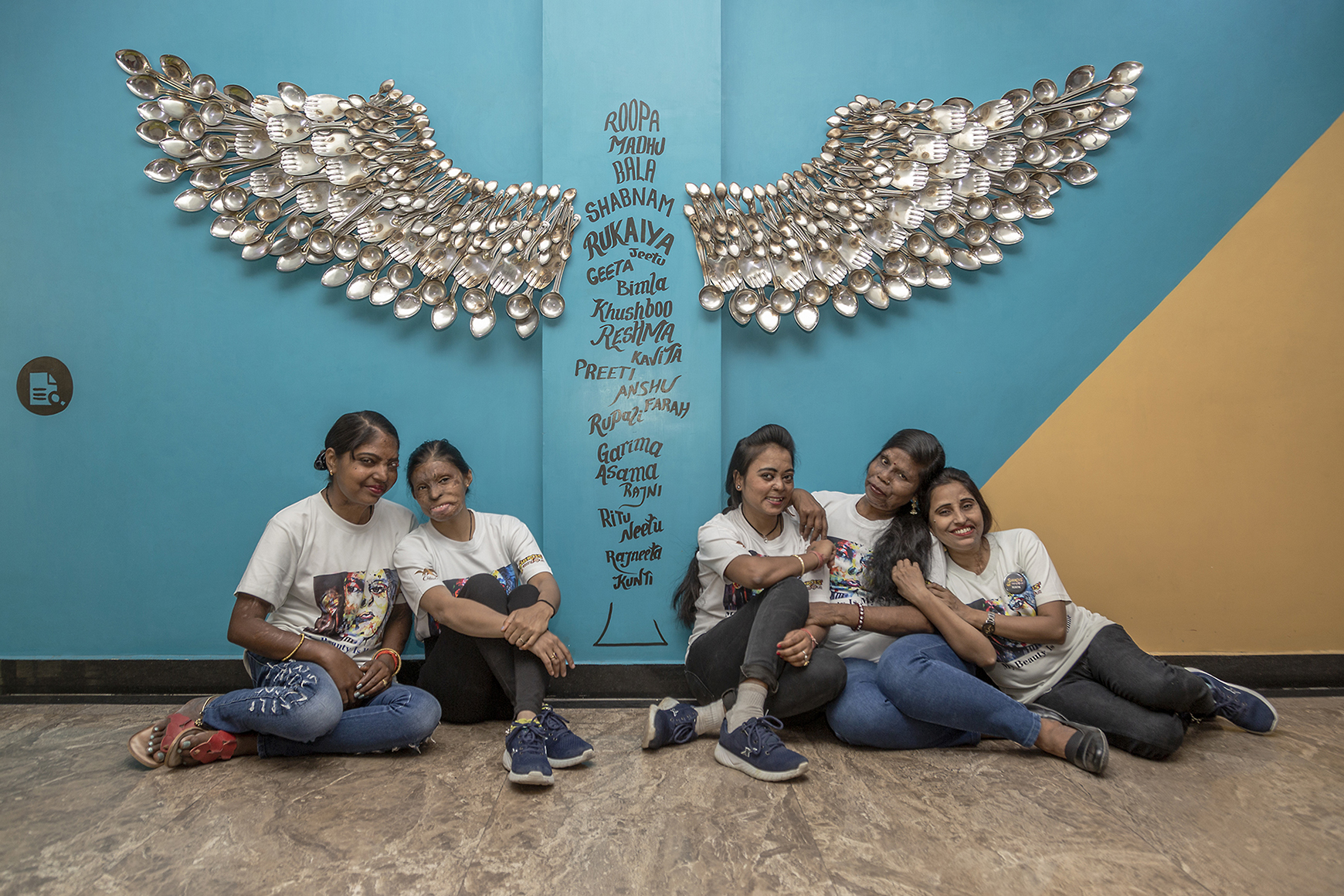 The Sheroes sit in relaxed poses on the floor of the café. Behind and above them, fixed to the sky-blue wall, is a large pair of angel wings constructed out of shiny stainless steel spoons and ladles. The wings are on either side of a vertical column on which names of acid attack survivors are painted in black in different sizes in both upper and lower case. They run from top to bottom of the column in this order: Roopa, Madhu, Bala, Shabnam, Rukaiya, Jeetu, Geeta, Bimla, Khushboo, Reshma, Kavita, Preeti, Anshu, Farah, Rupali, Garima, Asma, Rajni, Ritu, Neetu, Rajneeta, Kunti.