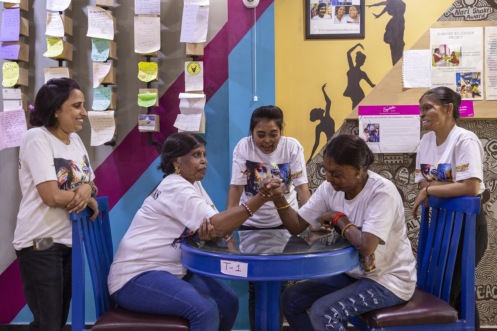 Sitting in blue plastic chairs on either side of a blue plastic table, Madhu on the left and Bala on the right are arm-wrestling while the others watch the contest. Rukaiya stands leaning against the back of Madhu's chair and Roopa similarly behind Bala's chair. Dolly faces us, leaning forward with both hands resting on the table and looking directly at the clutched right hands of the contestants. Behind them hanging on the wall are handwritten notes and posters.