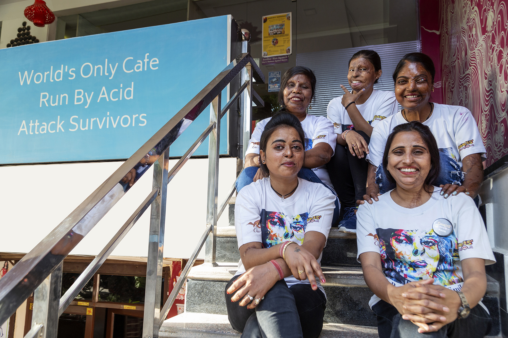"""The Sheroes dressed in their uniform of jeans and white T-shirt sit on the front steps of the café. Front row: Dolly and Rukaiya. Back row: Madhu, Roopa and Bala. To their left is a large sky-blue board with white lettering that says """"World's only café run by acid attack survivors""""."""