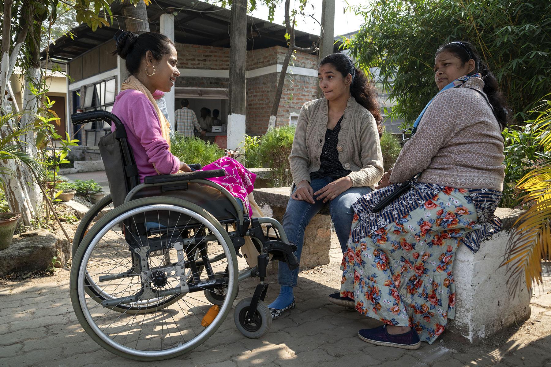 বাগানে পাথরের বেঞ্চিতে বসে আছে সিমি আর রুণু। সিলসিলা হুইলচেয়ারে বসা। ওরা তিনজন গল্প করছে।
