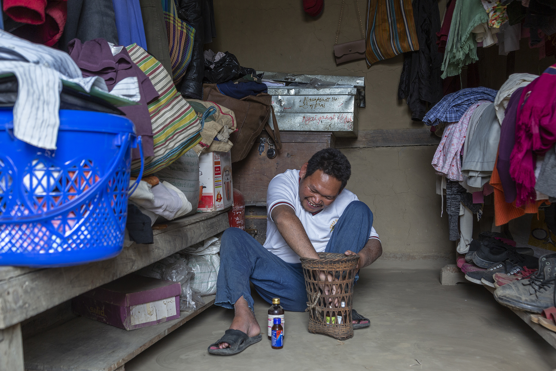Sohkho in white T-shirt and bluish grey pants sits in a cramped space on the mud floor of a room, smiling as he reaches his hand into a narrow, woven cane basket containing a couple of small medicine bottles. Two similar bottles rest on the floor next to his foot. He is wedged between two wooden racks overflowing with clothes, cloth bags, cardboard boxes and shoes. Behind him are two tin trunks on top of a wooden chest.