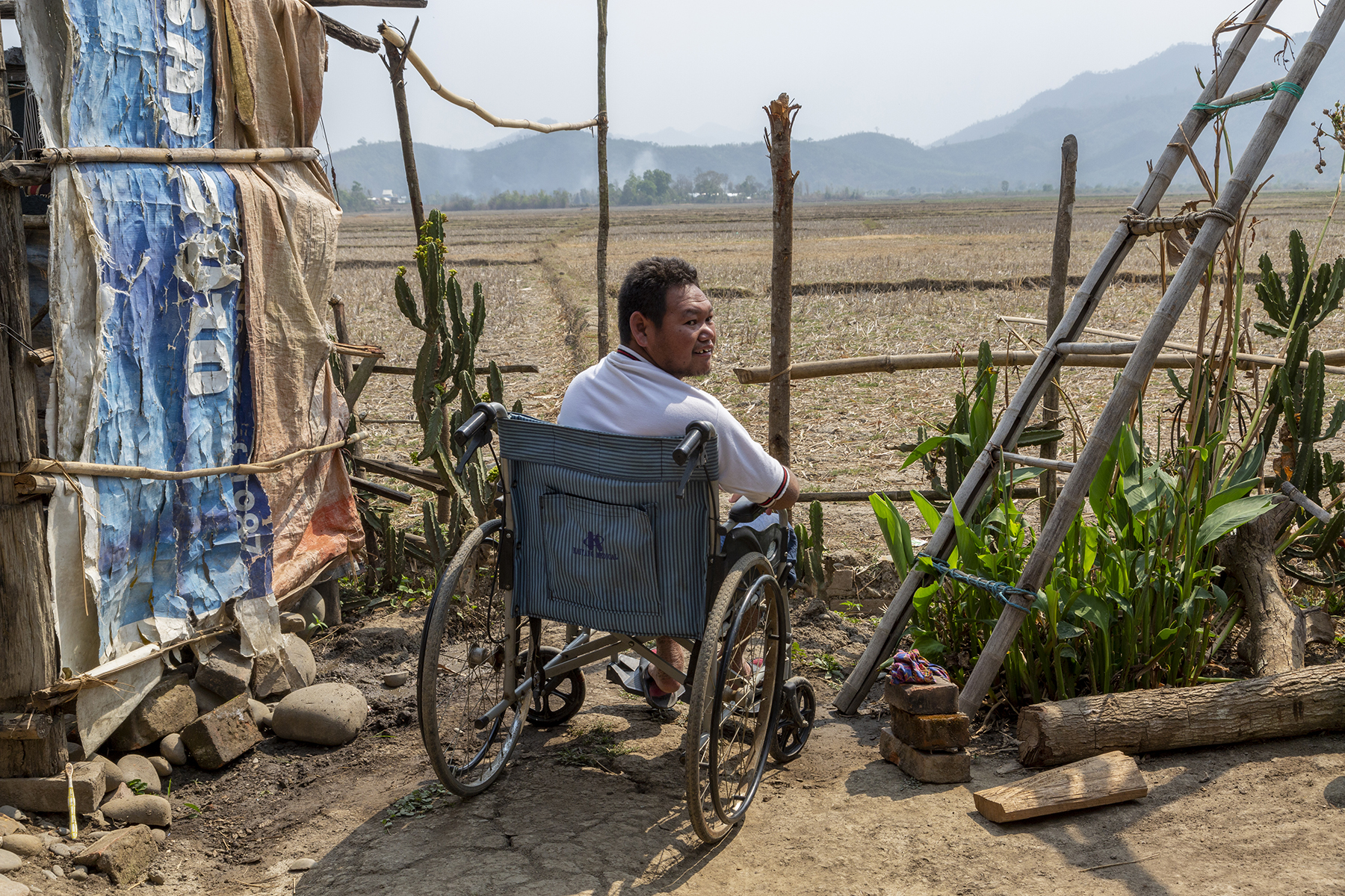 Sohkho sits in his wheelchair next to a fence made of upright branches and bamboo struts. The wheelchair, with its back to us, faces a landscape of harvested fields with brown stubble, and distant, misty blue hills. He wears a white T-shirt and has turned his body sideways so that he shows his profile. To the right of the wheelchair beneath an inclined bamboo ladder are a few canna and cactus plants.